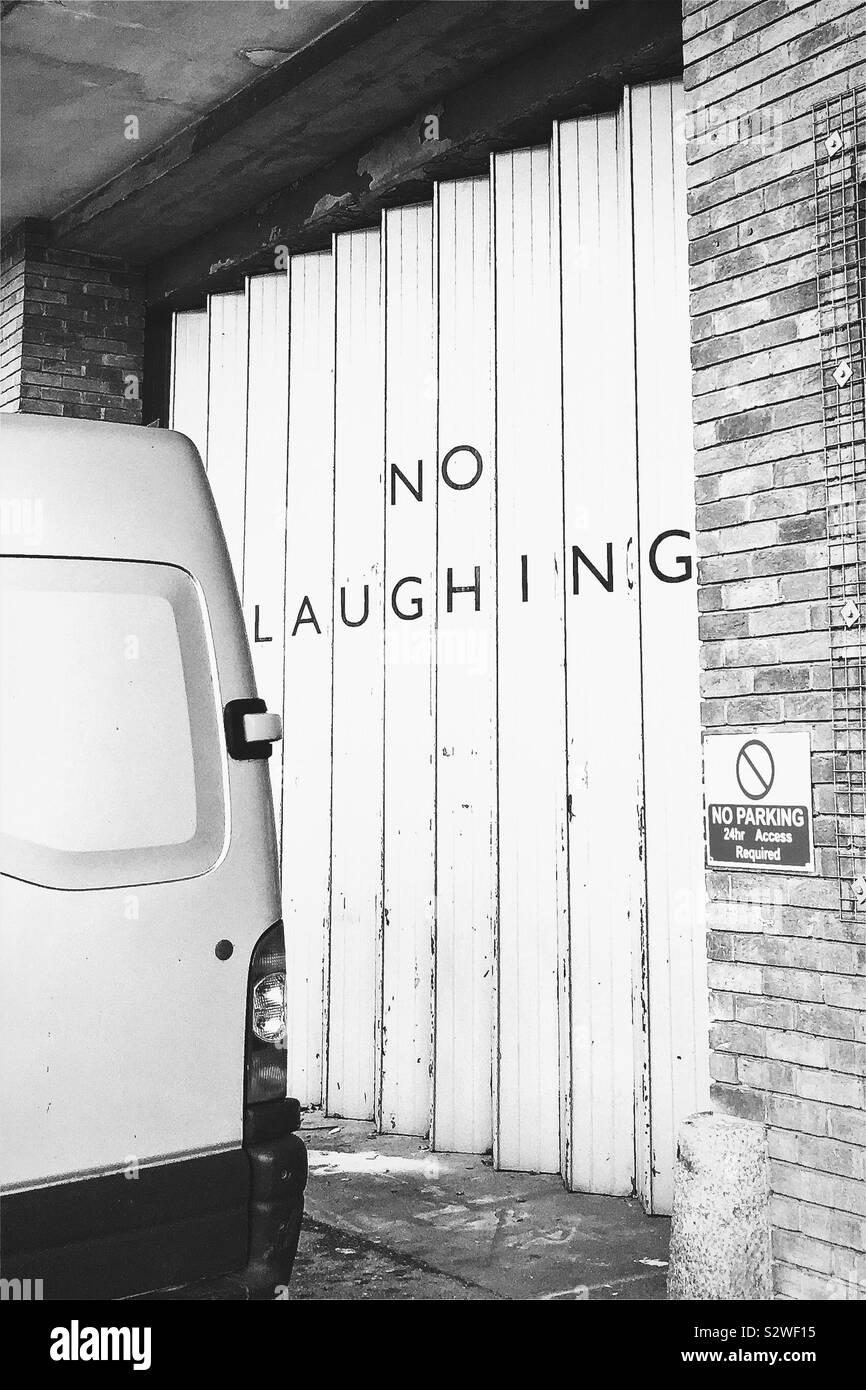 'Keine Lachende' Wörter auf Zickzack Garagentore bei Spike Island, Bristol, Großbritannien Stockfoto