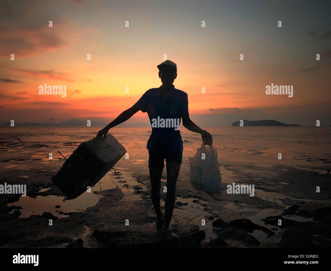 Fischer zu Fuß in den Schlamm mit seinen Fang bei Sonnenuntergang in Kuala Perlis, Malaysia Stockfoto