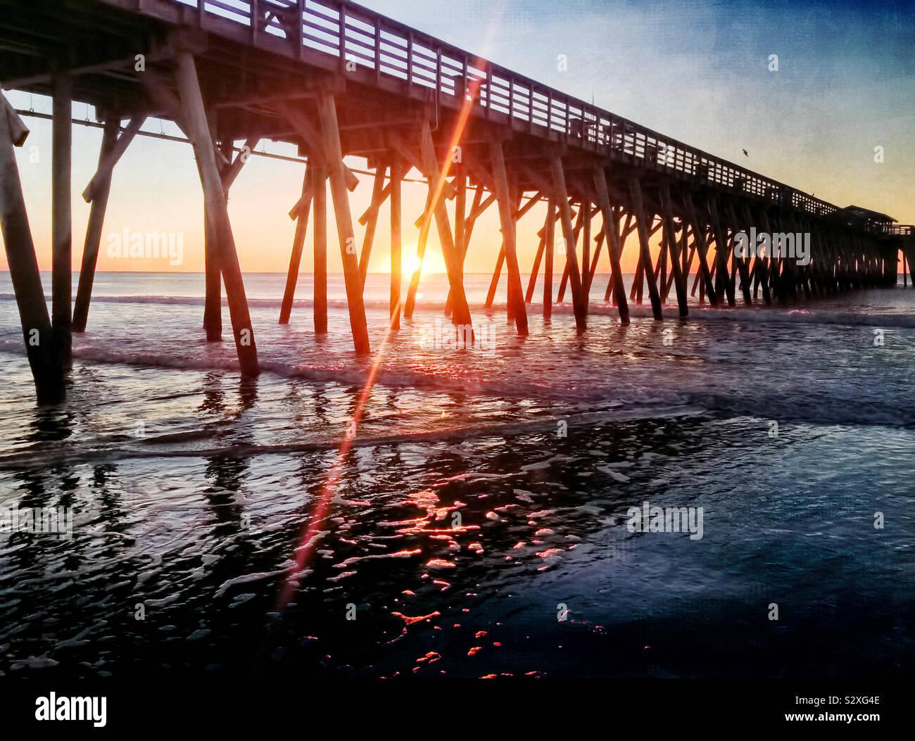 Sonnenaufgang hinter einem Pier in Myrtle Beach, South Carolina. Die hellen Lichtreflexionen von der aufgehenden Sonne schafft visuelles Interesse. Stockfoto