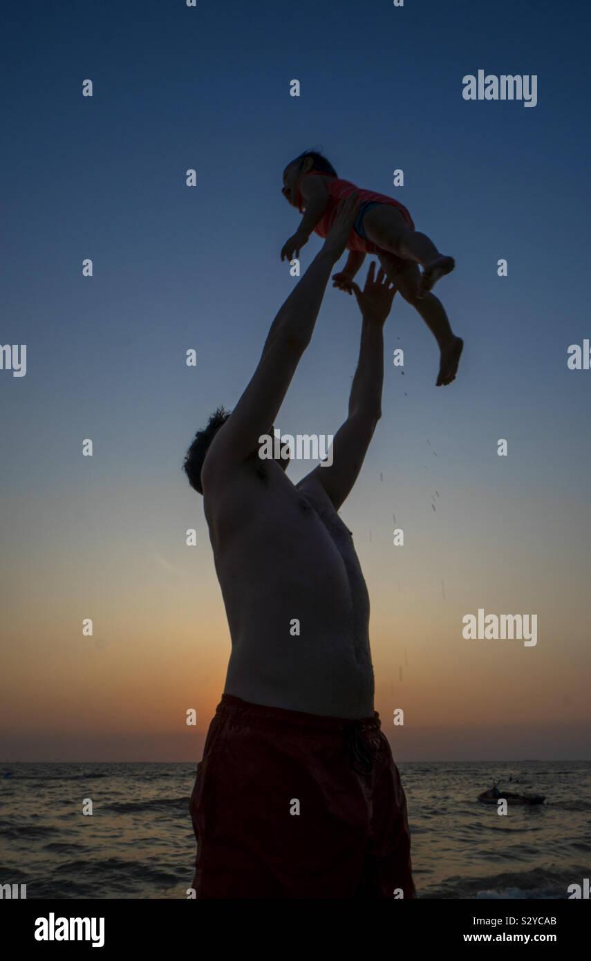 Papa spielt mit Tochter am Strand Stockfoto