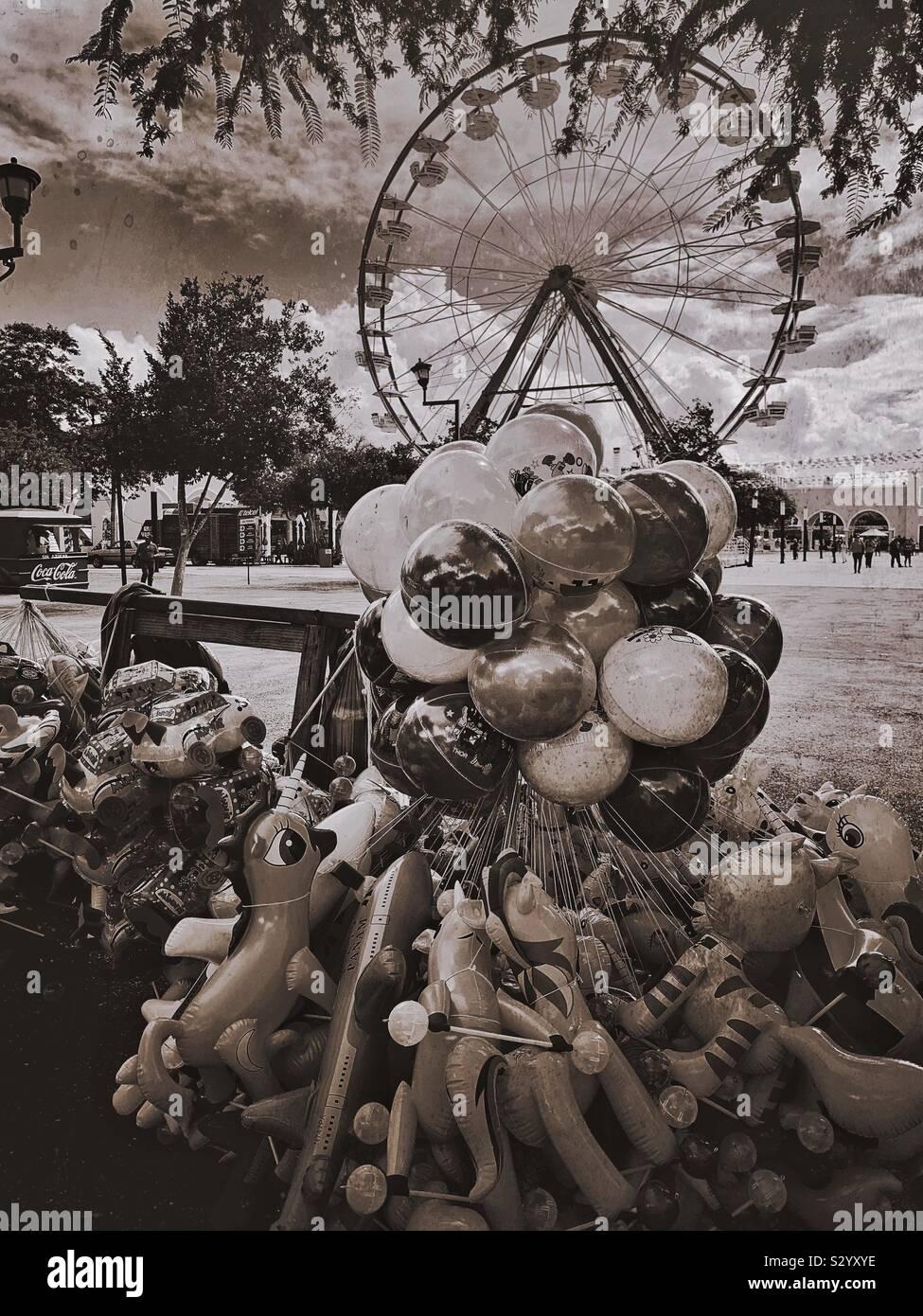 Ein Cluster von Luftballons und ein Riesenrad sind Teil der Familie freundlich und spannenden Umfeld an der Feria Yucatán Xmatkuil. Stockfoto