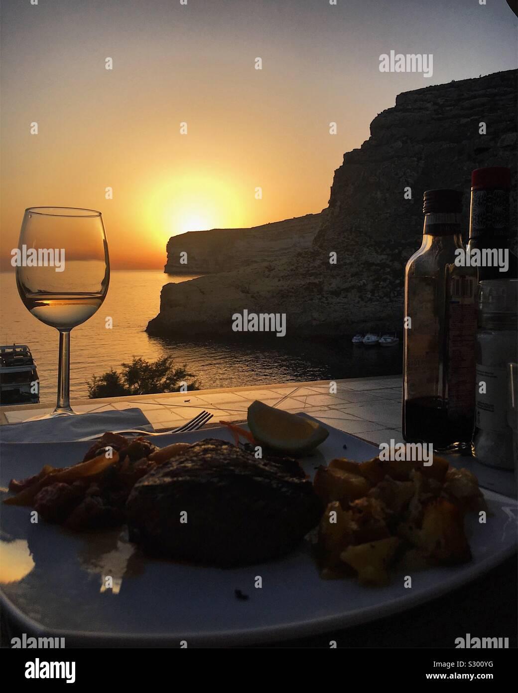Restaurant am Meer mit Sonnenuntergang im Hintergrund. Stockfoto