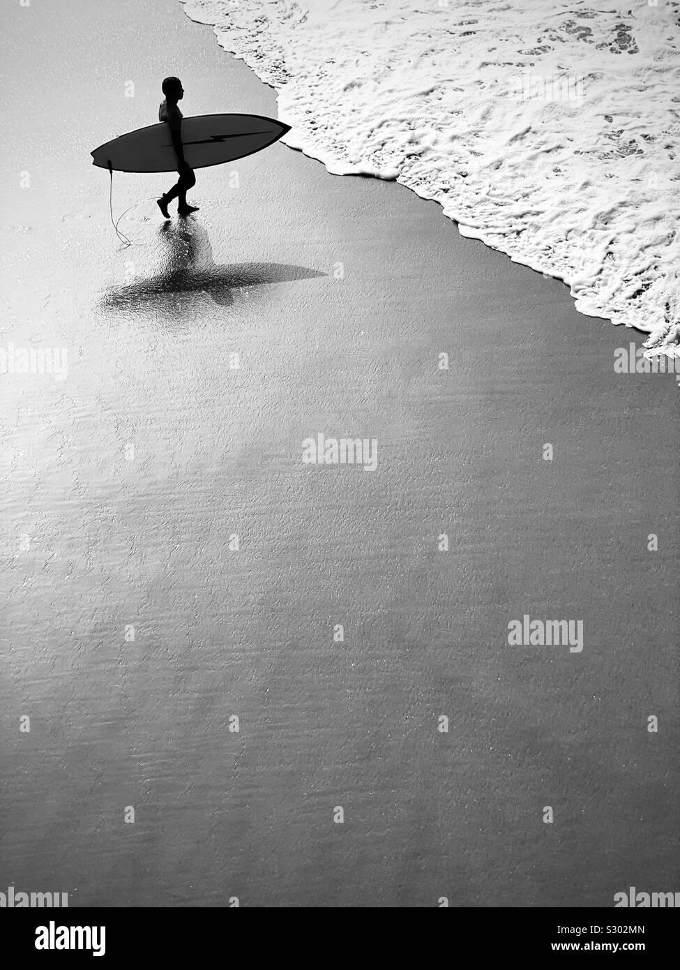 Männliche Surfer Spaziergänge in die Brandung. Manhattan Beach, Kalifornien, USA. Stockfoto