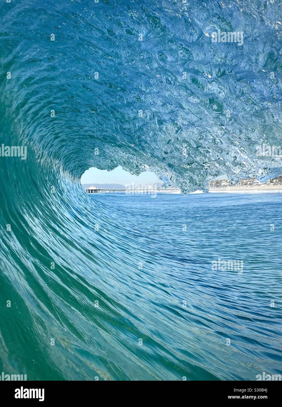 Innen aus einem fässerfüllen Wave mit Manhattan Beach Pier im Hintergrund. Manhattan Beach, Kalifornien, USA Stockfoto