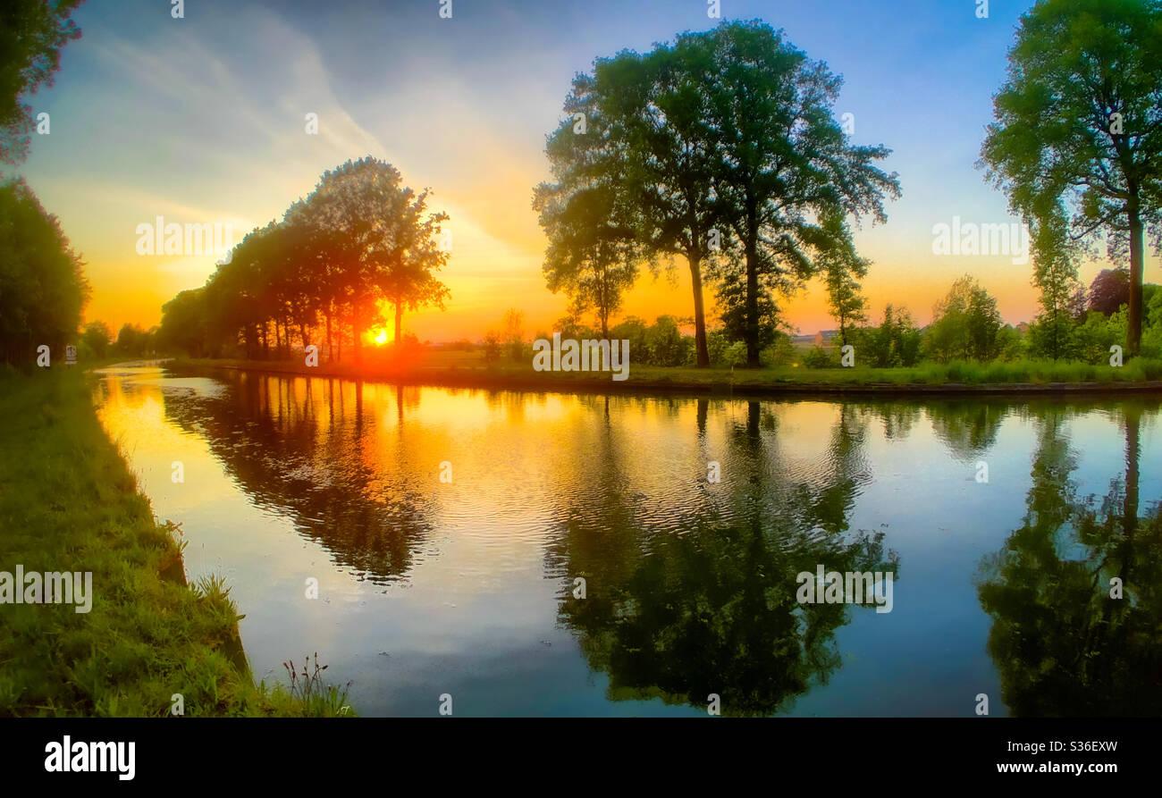 Leuchtend orangefarbener roter Sonnenuntergang spiegelt sich im Wasser des Flusses wider Stockfoto