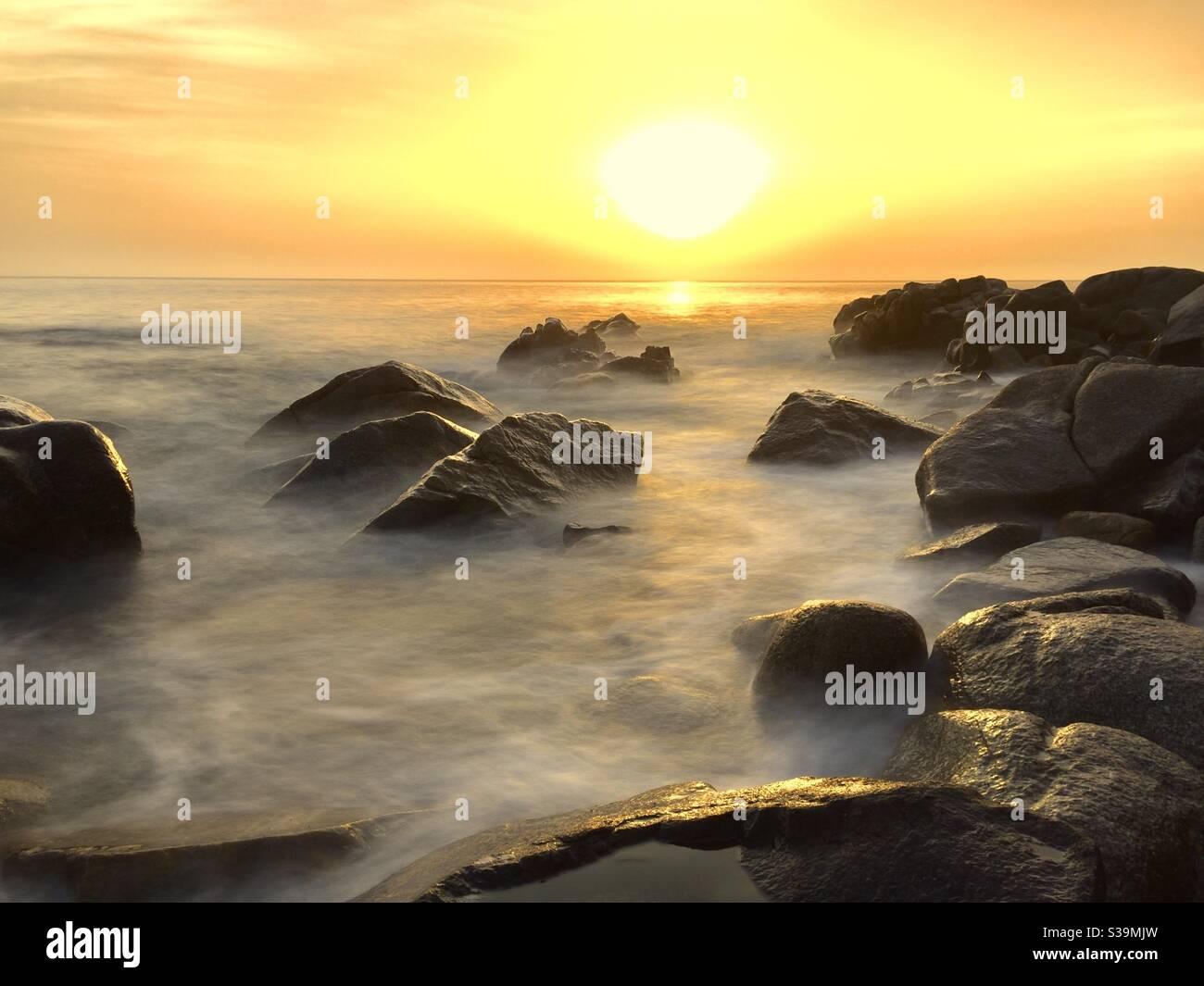 Nebliger Sonnenuntergang am Meer Stockfoto