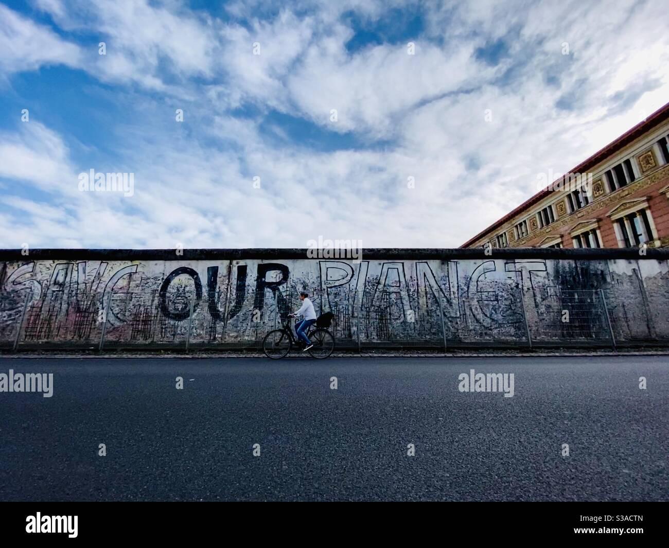 """Eine Frau fährt mit dem Fahrrad entlang eines Teils der Berliner Mauer, der noch oben ist. Graffiti an der Wand lautet """"rette unseren Planeten"""". Berlin, Deutschland. Stockfoto"""