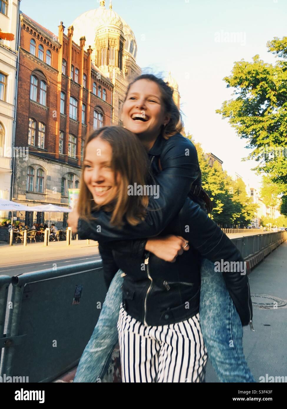 Mädchen Huckepack und lachen Stockfoto