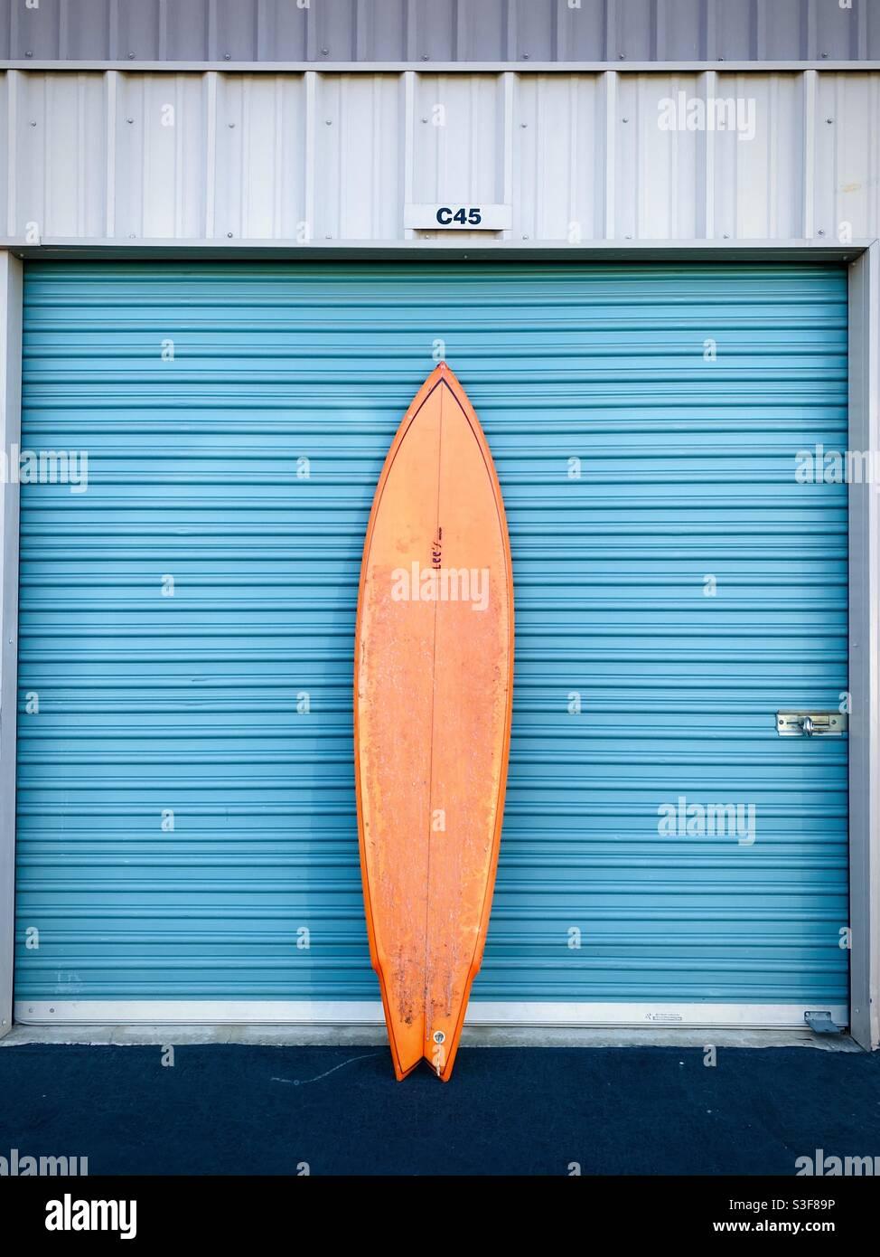 Ein orangefarbenes Surfbrett gegen eine Garage. Stockfoto