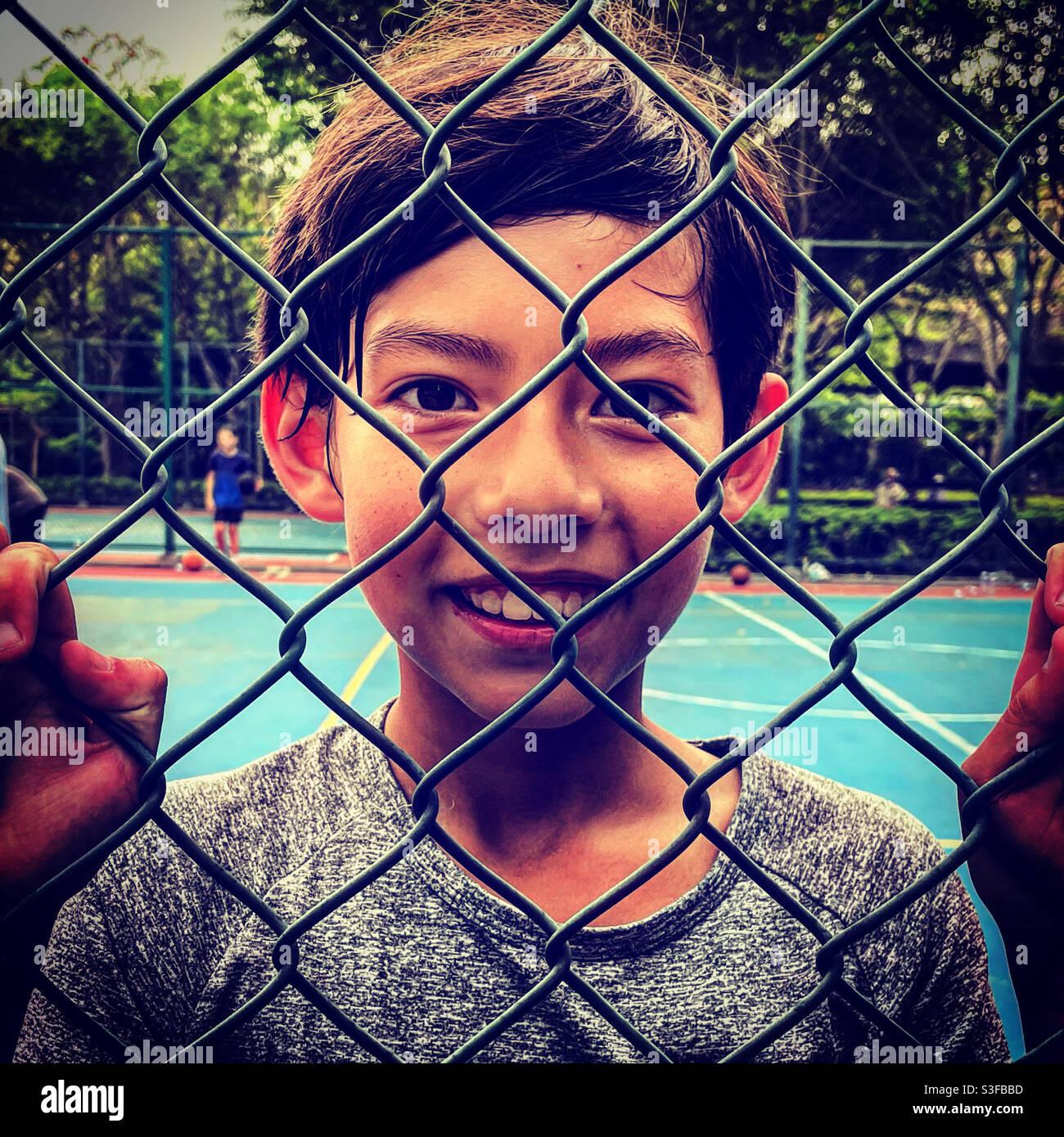 Fröhlicher und lächelnder Junge durch einen Gitterzaun Ein Basketballspielplatz im Freien Stockfoto