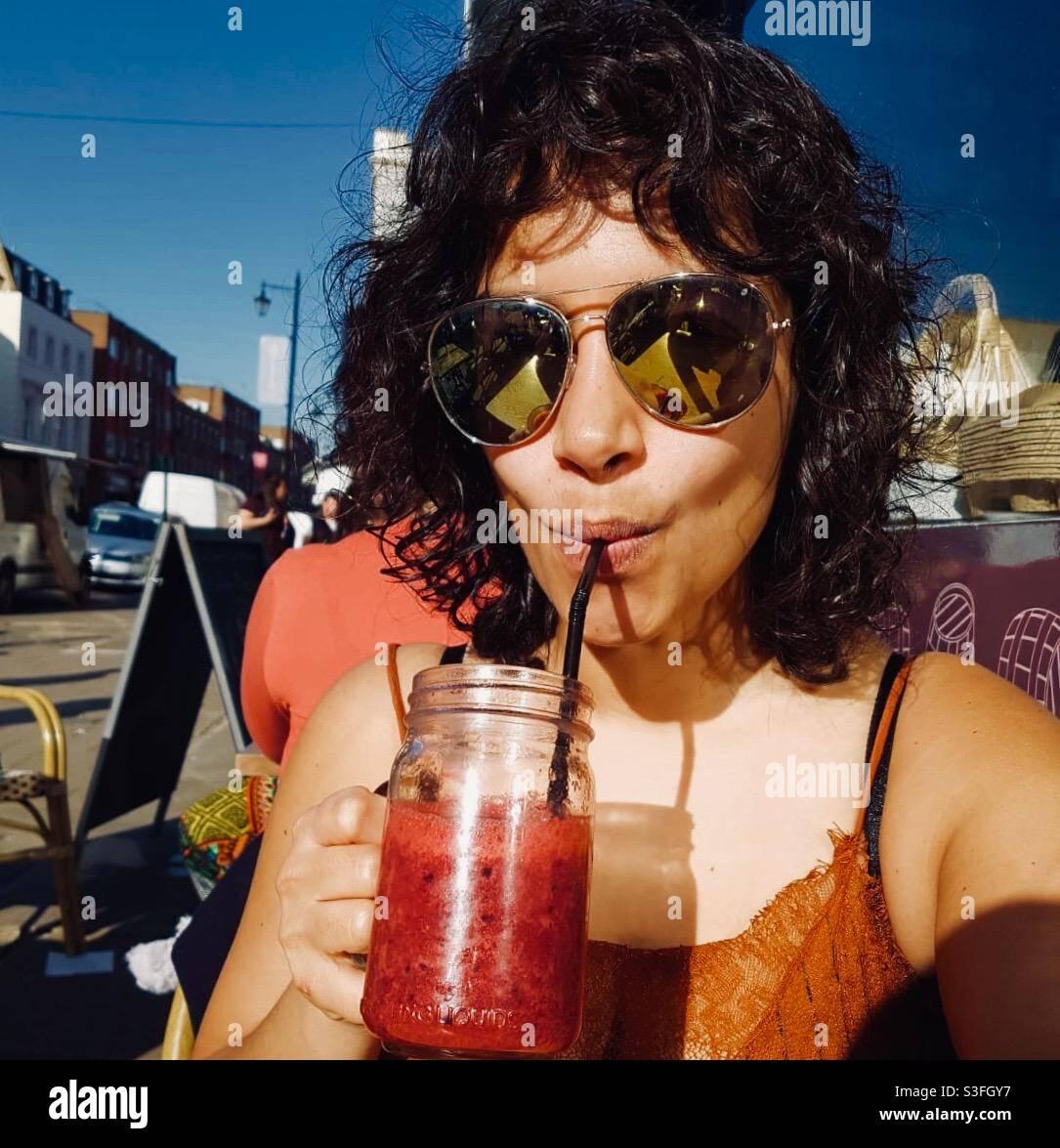 Lockig haarige Mädchen große Sonnenbrille trinken roten Cocktail Smoothie in einem Glas in der Sonne. Stockfoto