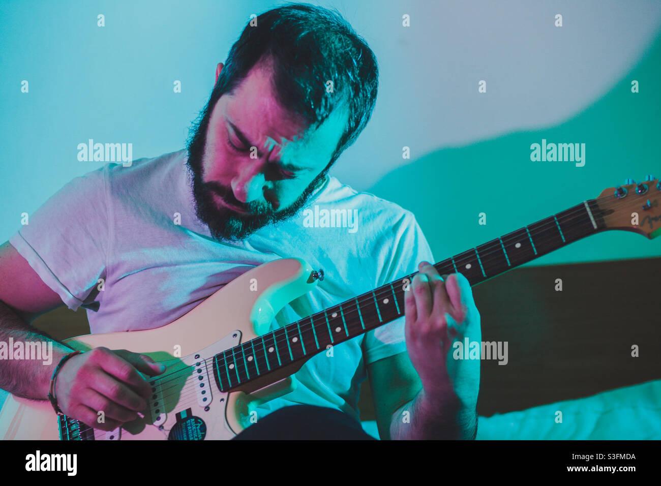 Ein Gitarrist, der solo, pink und blau leuchtet Stockfoto