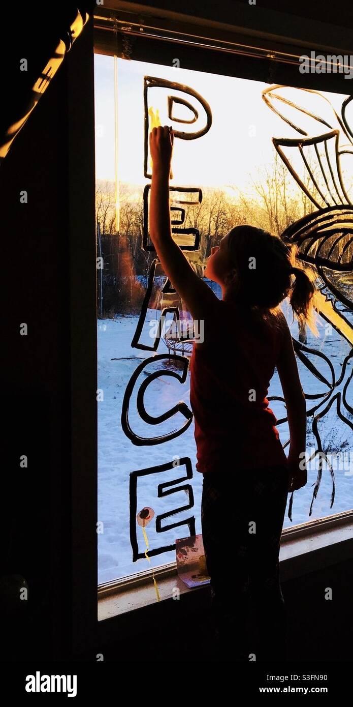 Mädchen malt eine Fensternachricht. Stockfoto