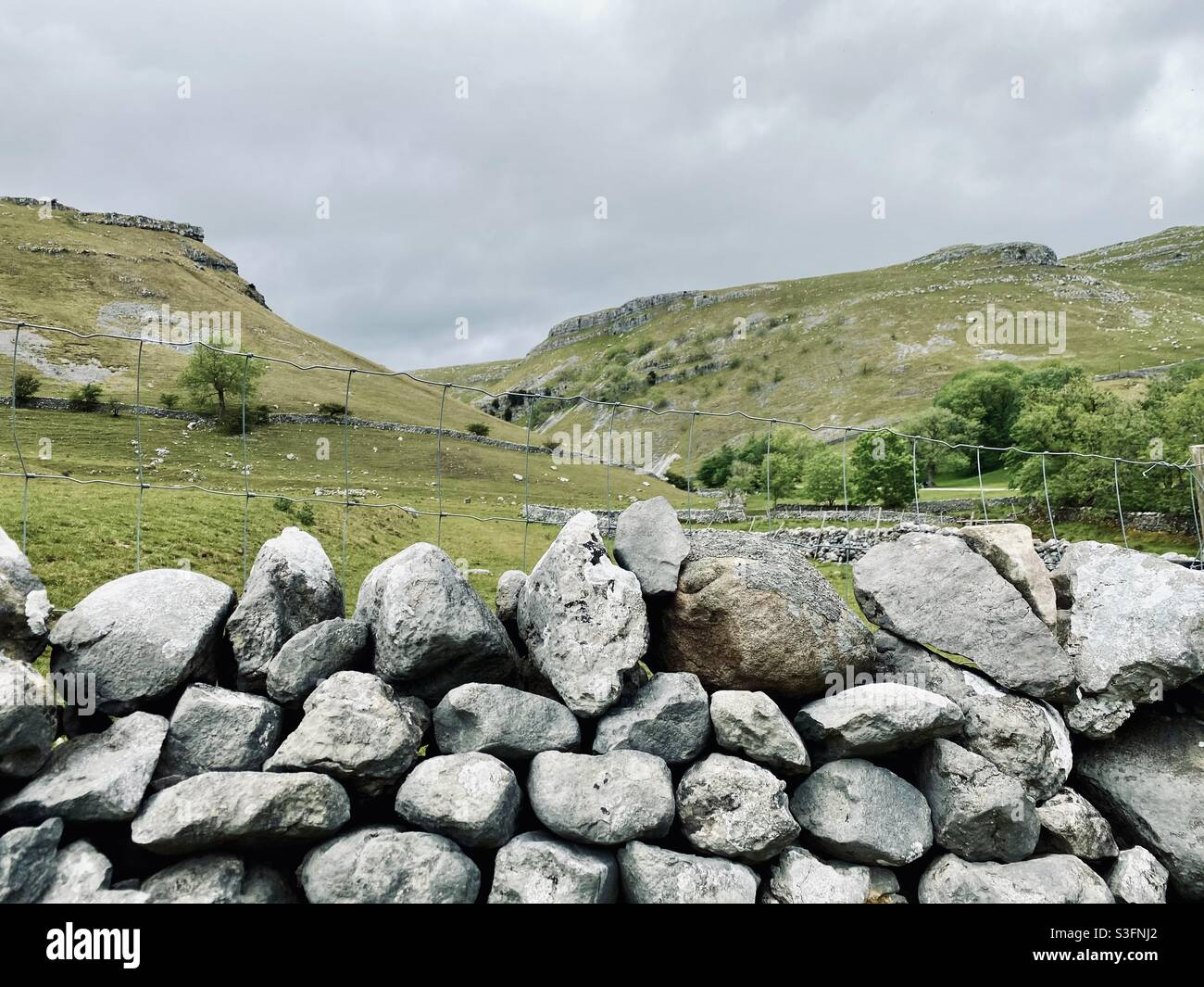 Malerische ländliche Landschaft mit dramatisch grauem Himmel in Malham, Yorkshire Dales National Park, Großbritannien. Sanfte Hügel und grüne Weiden mit Trockenmauern Stockfoto