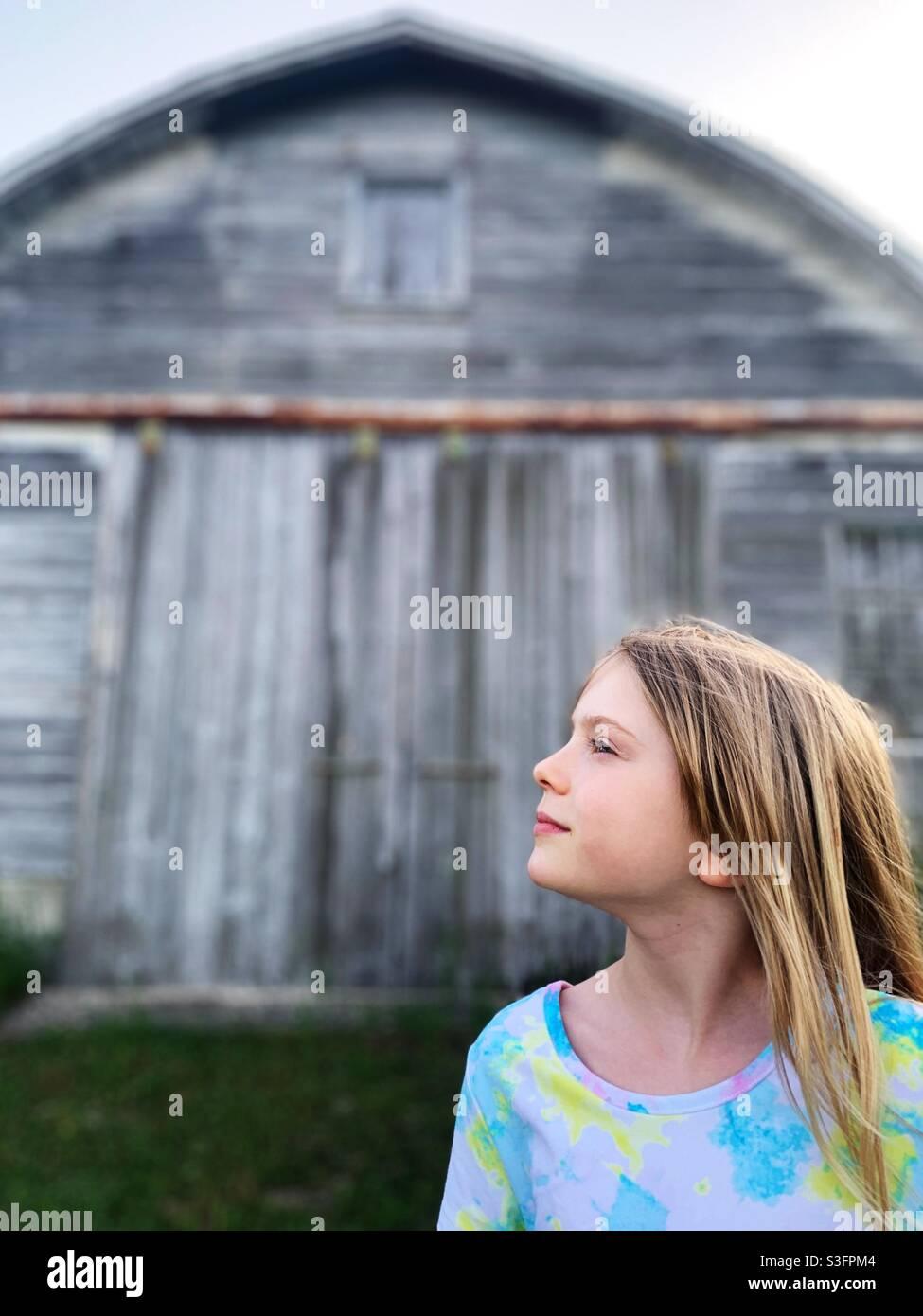 Ein junges blondes Kind, das in der Ferne vor einer alten Scheune steht Stockfoto