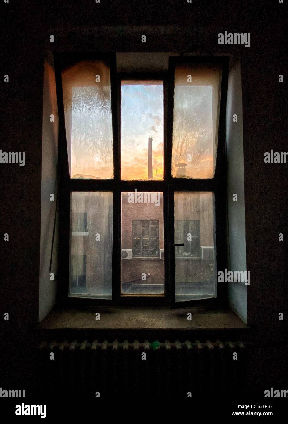Altes, dreckiges Fenster mit Sonnenuntergangshimmel und Fabrikrohr Stockfoto