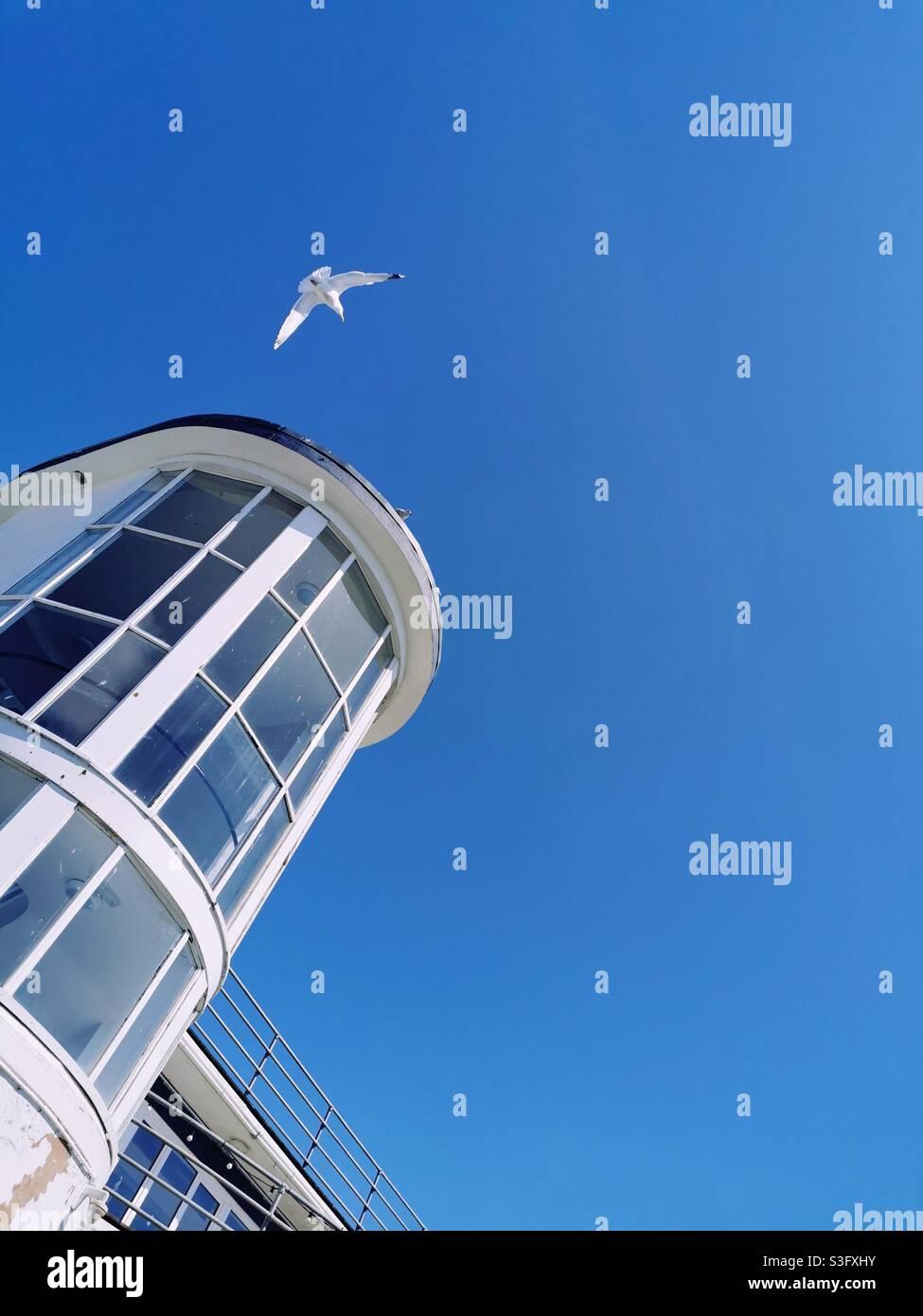 Weißer Turm und Möwe gegen blauen Himmel Stockfoto
