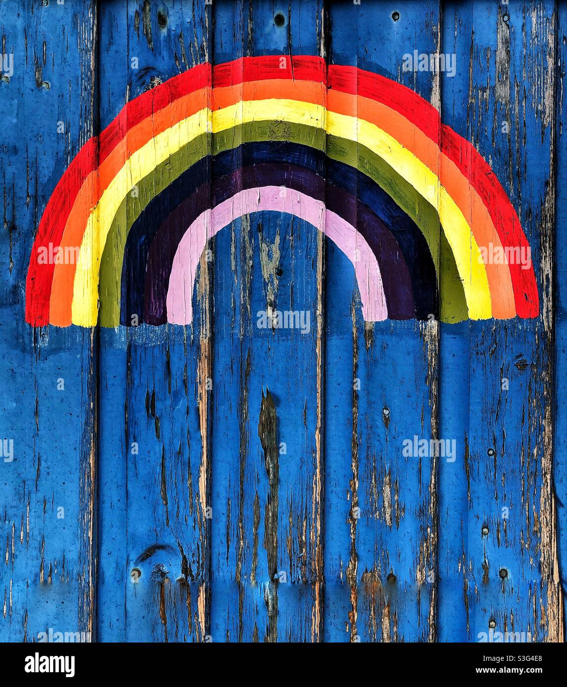 Ein farbenfroher Regenbogen, der auf eine strukturierte Holztür gemalt wurde, von Kindern, die dem britischen Gesundheitsministerium danken Stockfoto
