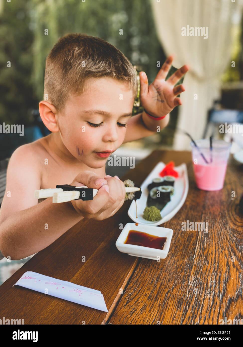 Fünf Jahre alter Junge, der draußen Sushi isst und einen Milchshake trinkt Stockfoto