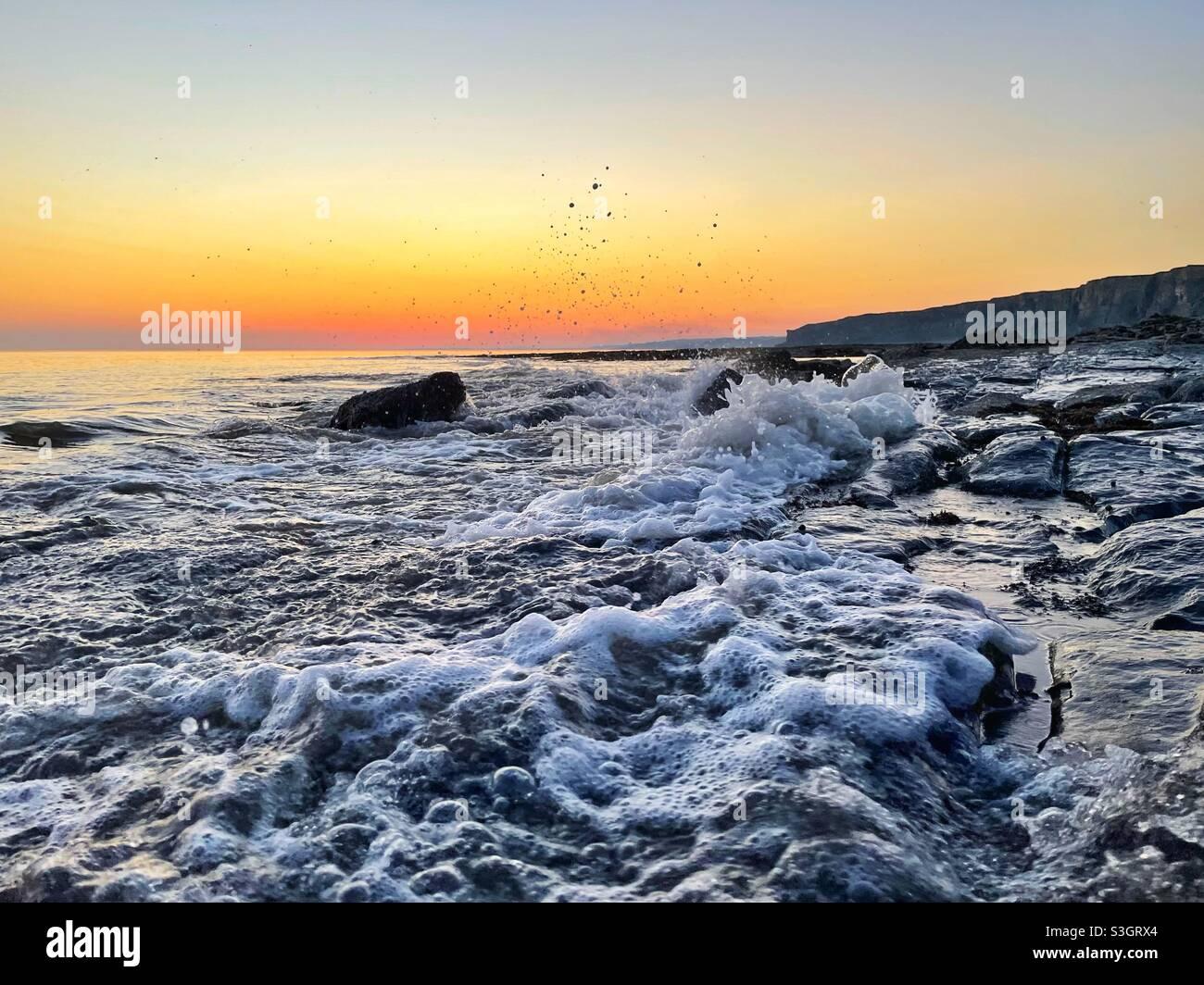 Sprudelndes Meer an der Küste von Südwales bei Dämmerung, ankommender Flut. Stockfoto