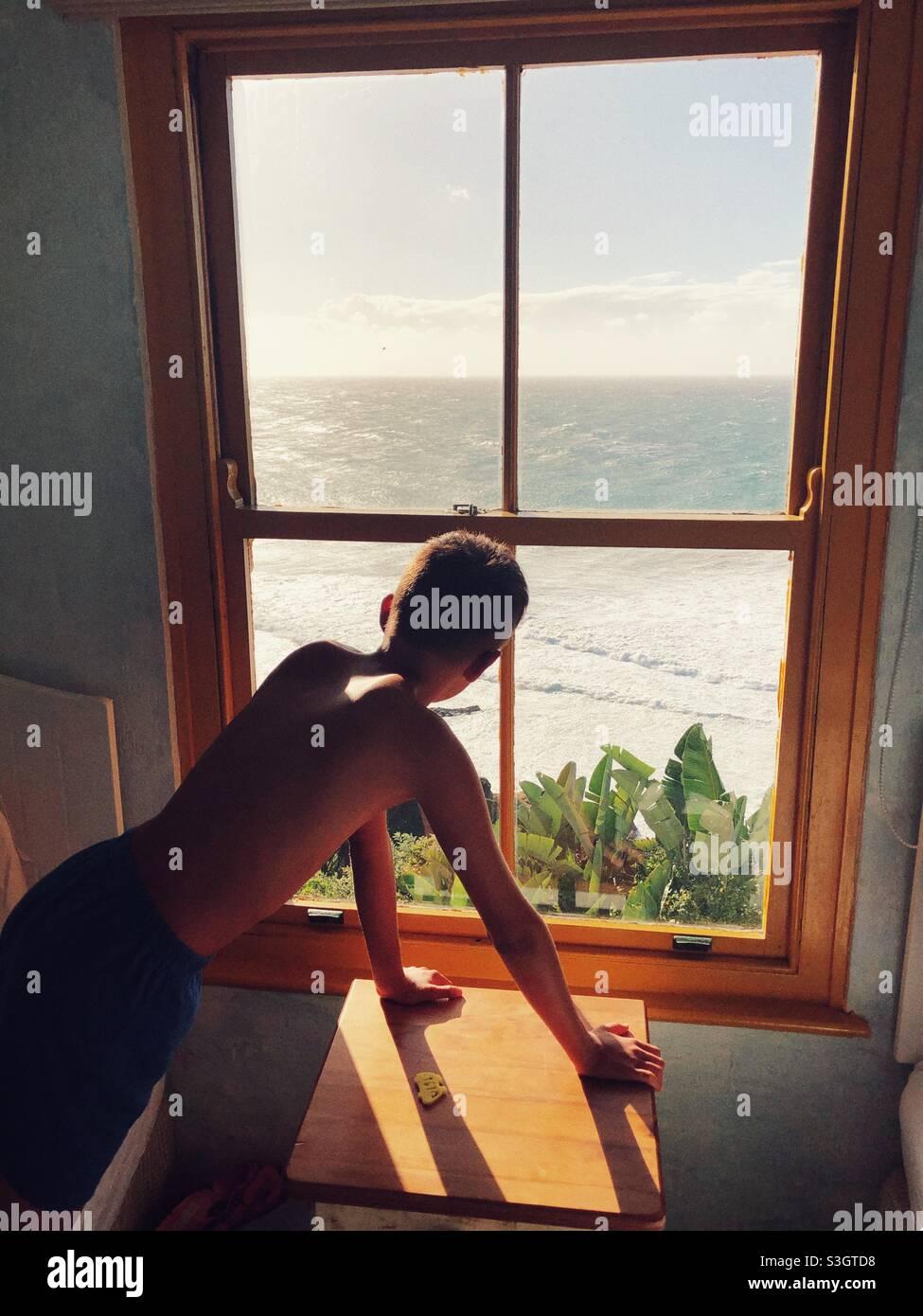 Ein kleiner Junge, der aus dem Fenster auf den Sonnenaufgang über dem Indischen Ozean blickt Stockfoto