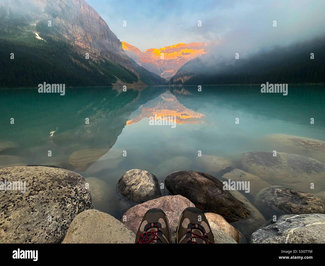 Füße am Rande eines Lake Louise-Sonnenaufgangs Stockfoto
