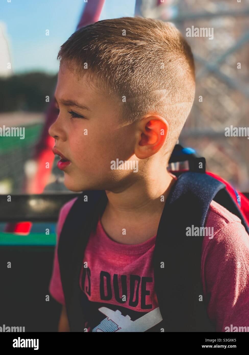 Die fünfjährige sitzt auf einem Riesenrad und schaut sich die verschiedenen Attraktionen an Stockfoto
