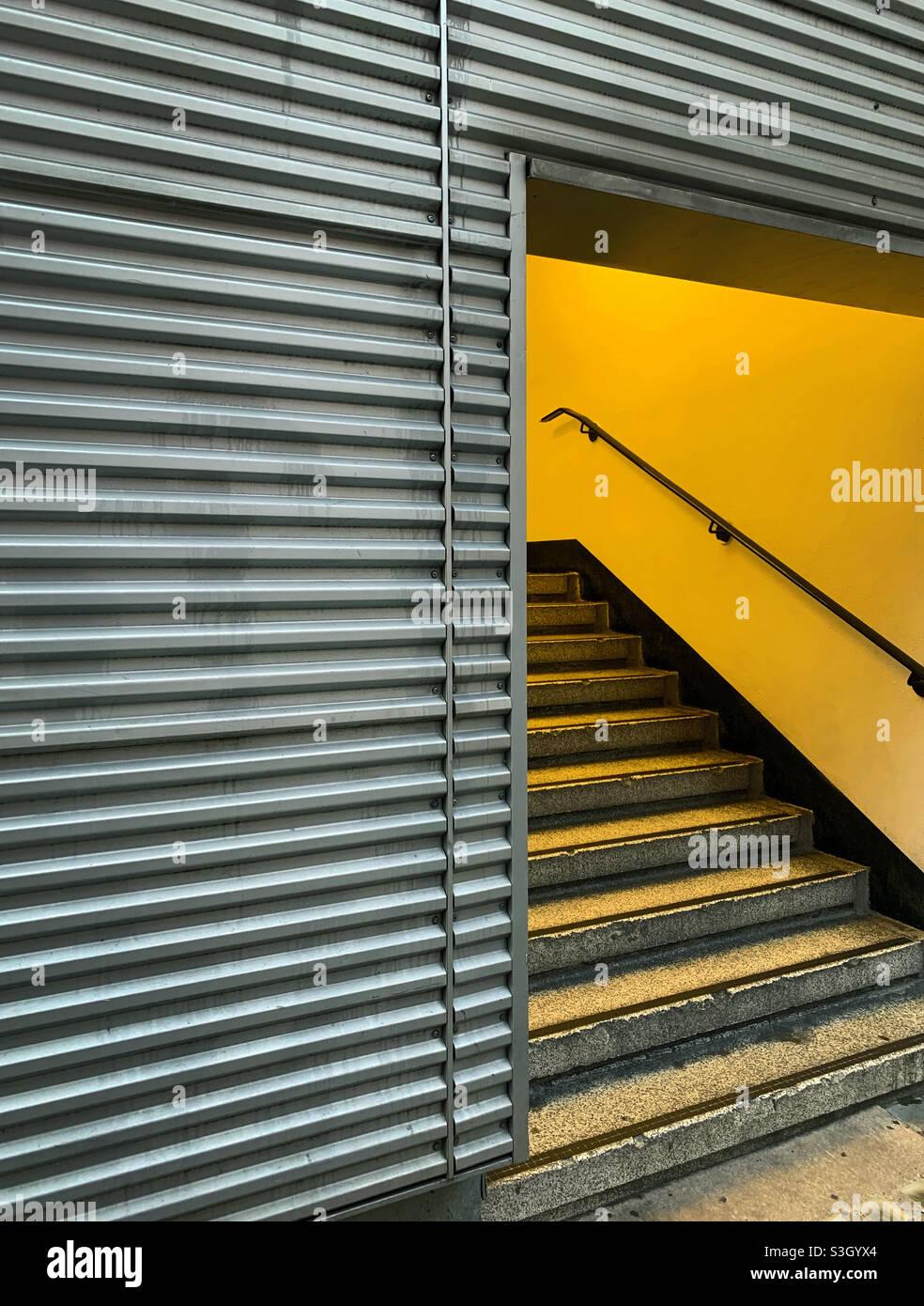 Eine in gelbes Licht getauchte Treppe, die aus EINEM metallverkleideten Gebäude auftaucht Stockfoto