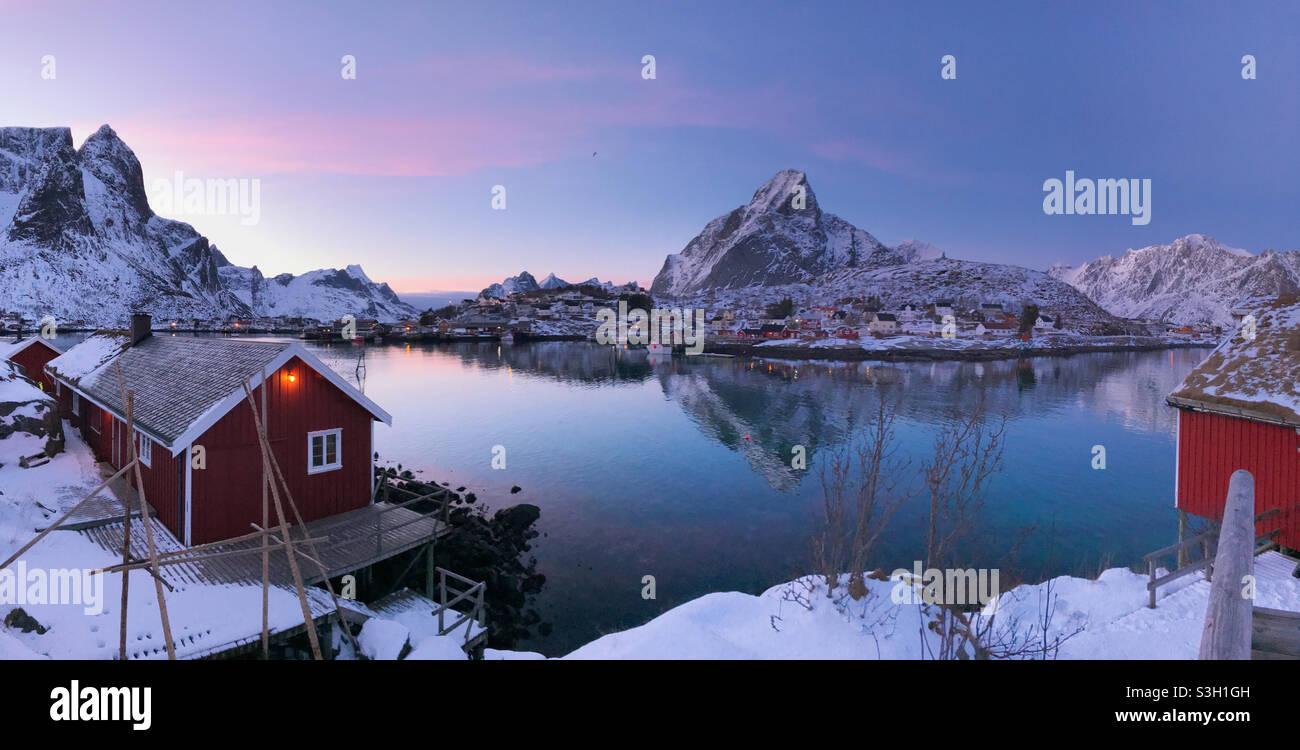 Schönes Fischerdorf reine im Winter, Lofoten-Inseln, Norwegen. Farbenfroher Sonnenuntergang über dem schönen Fischerdorf reine, umgeben von schneebedeckten Fjorden. Stockfoto