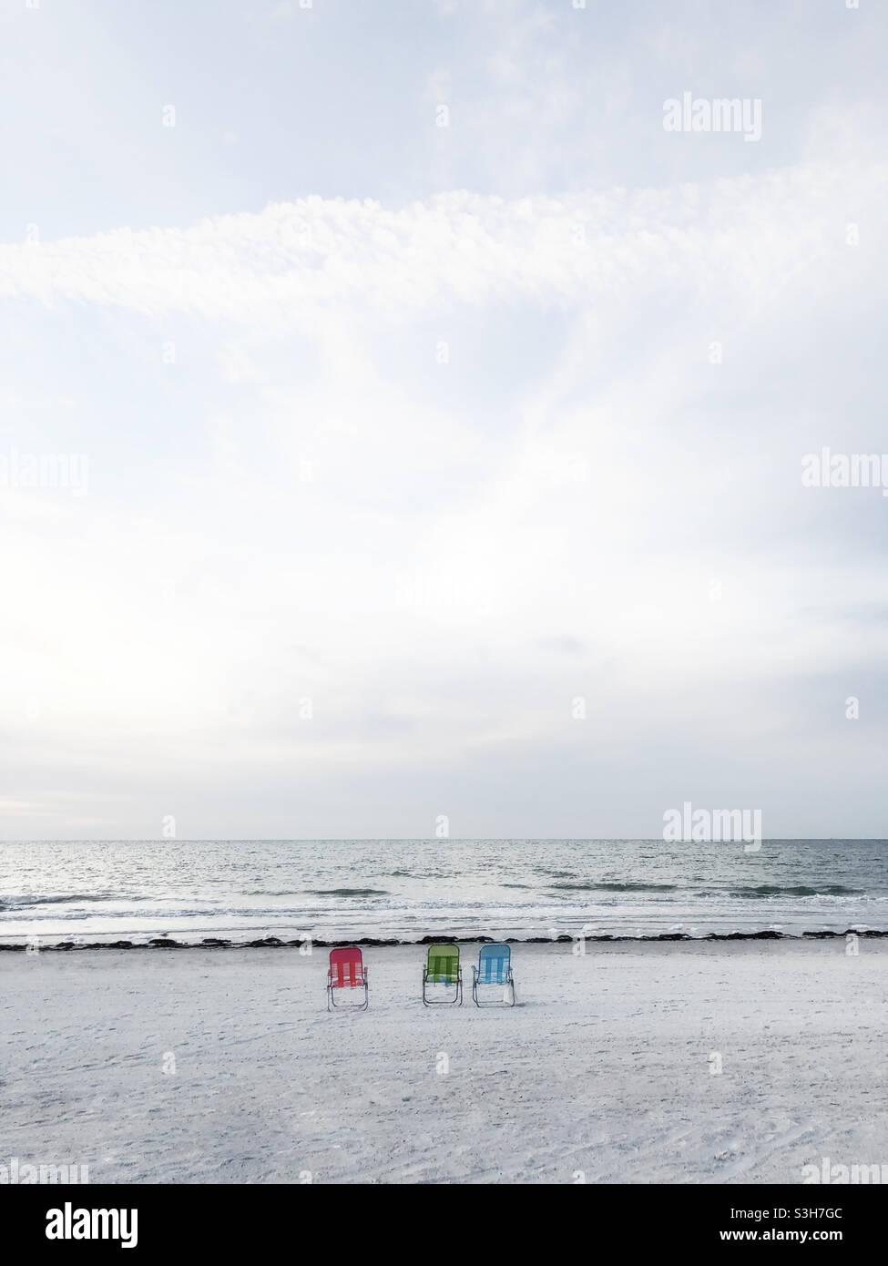 Drei Liegestühle am Strand Stockfoto