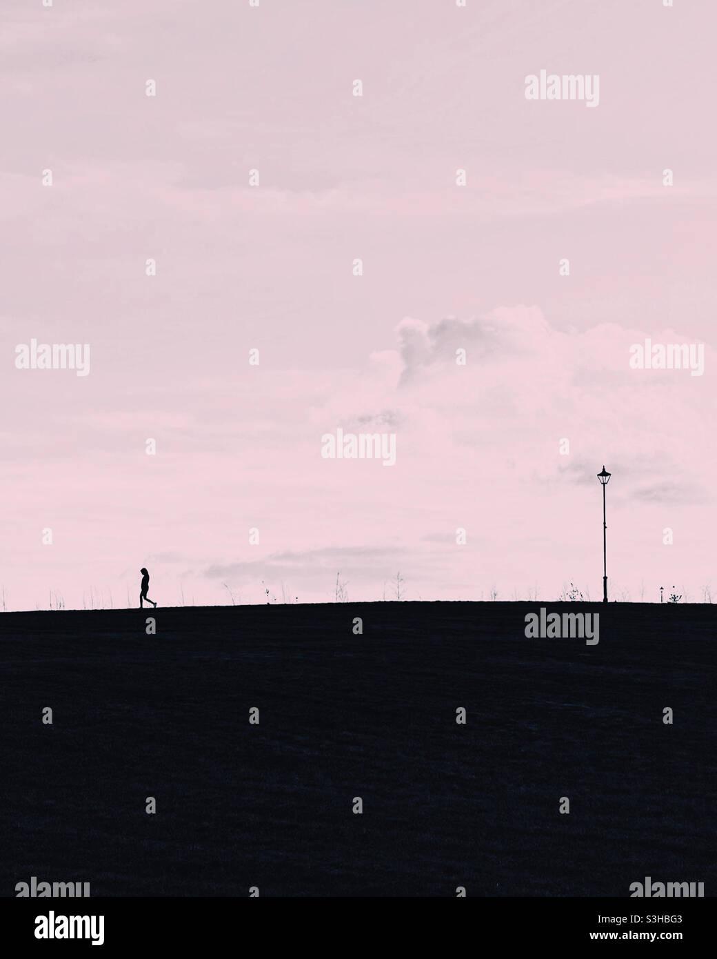Einone Silhouette auf einem Hügel mit Laternenpfosten. Stockfoto