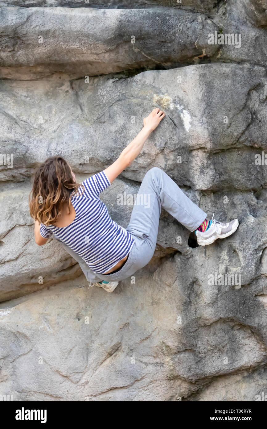 Junge Frau mit langen Haaren hängen an einem felsigen Gesicht eines Berges, während Sie Klettern ohne Seil Unterstützung Stockbild