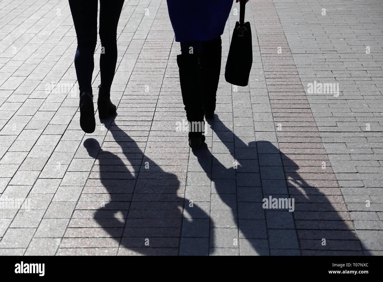 66232c2628d21c Zwei Frauen auf der Straße, schwarze Silhouetten und Schatten auf Pflaster.  Schlanke Beine in Stiefeln, Konzept der weiblichen Mode, Freundschaft, ...