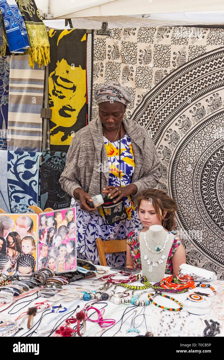 Ein junges Mädchen über die Haare von einem standbesitzer in Costa Adeje touristischen Markt auf der spanischen Insel Teneriffa. Stockbild