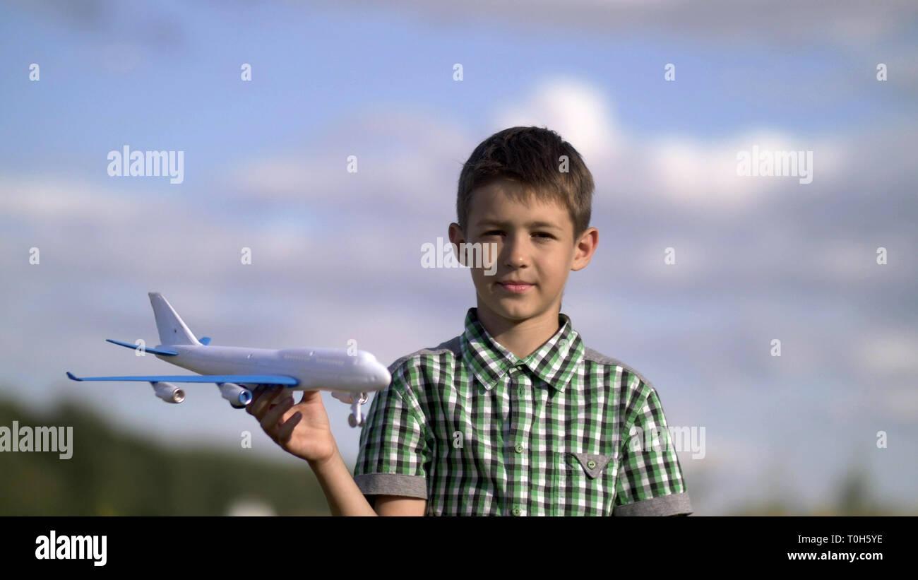 Happy Teen Boy spielen mit Spielzeug Flugzeug auf die Natur Stockbild