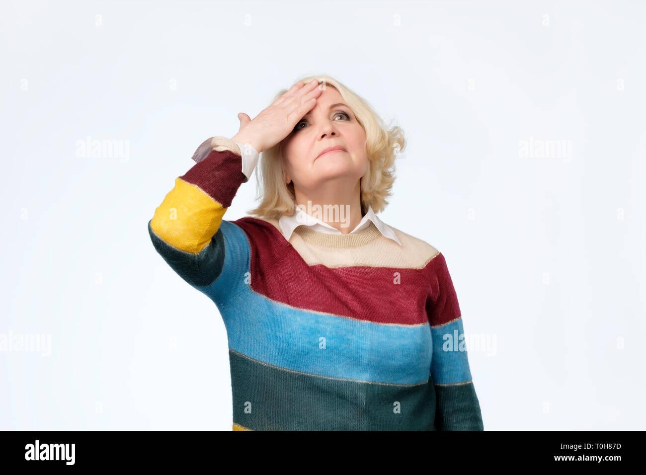 Ältere blonde Frau mit der Hand überrascht auf dem Kopf für Fehler, denken Sie daran, Fehler Stockbild