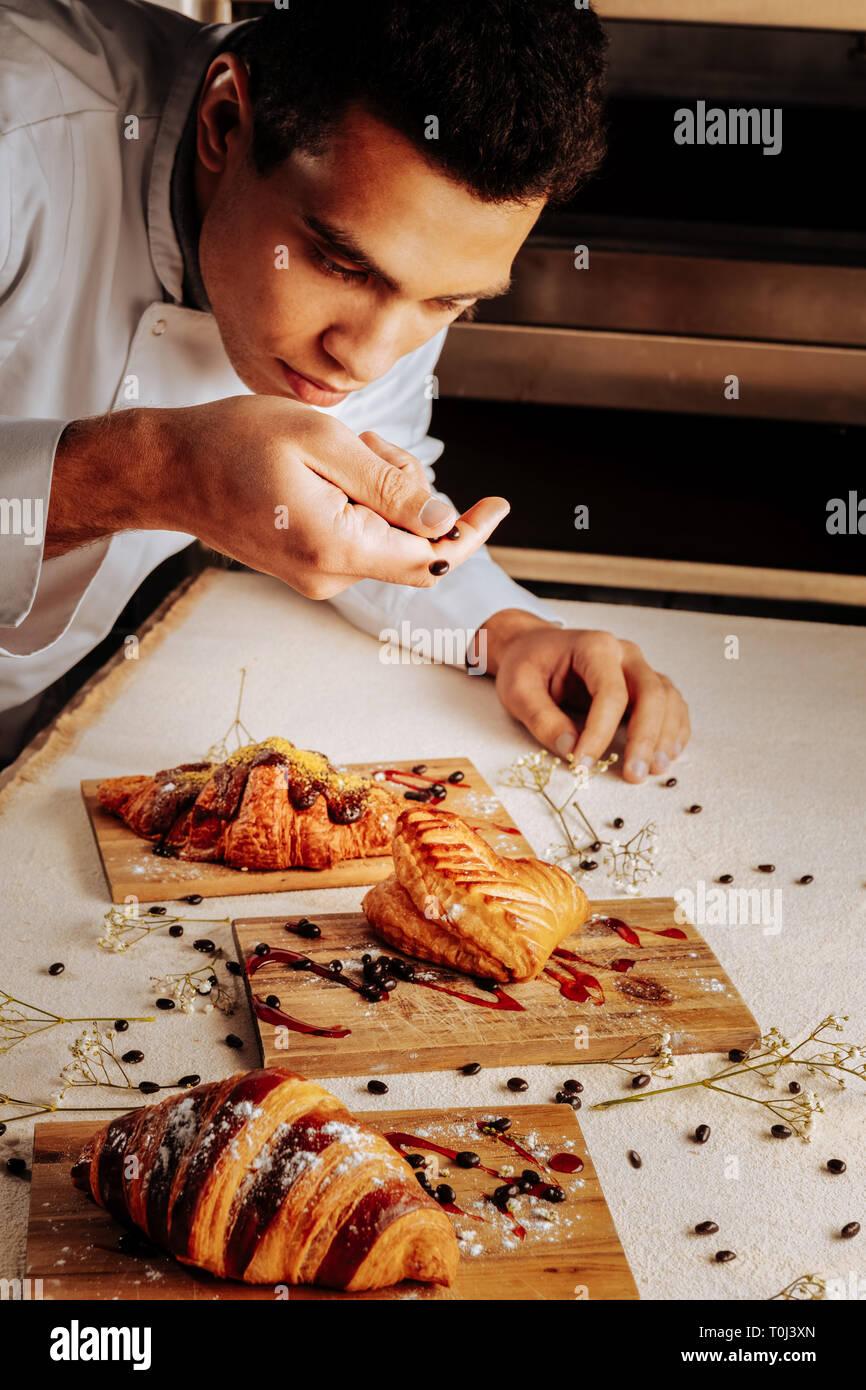 Baker dekorieren Gebäck Desserts mit Nüsse in Schokolade Stockbild