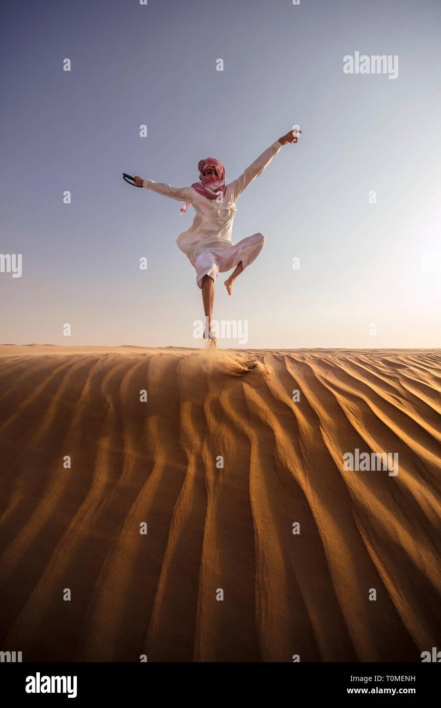 Ein saudischer Mann ist das Springen in Wüste, Saudi-Arabien Stockfoto