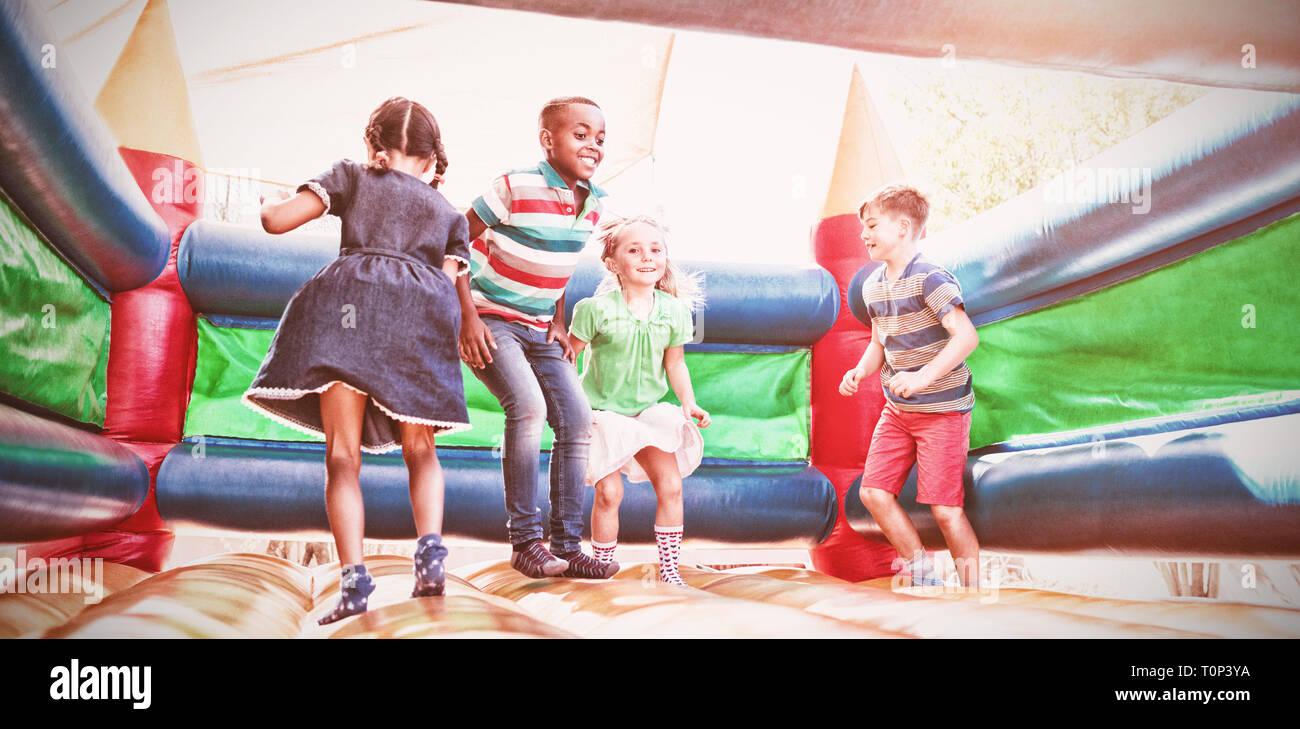 Freunde spielen auf Hüpfburg, Spielplatz Stockbild
