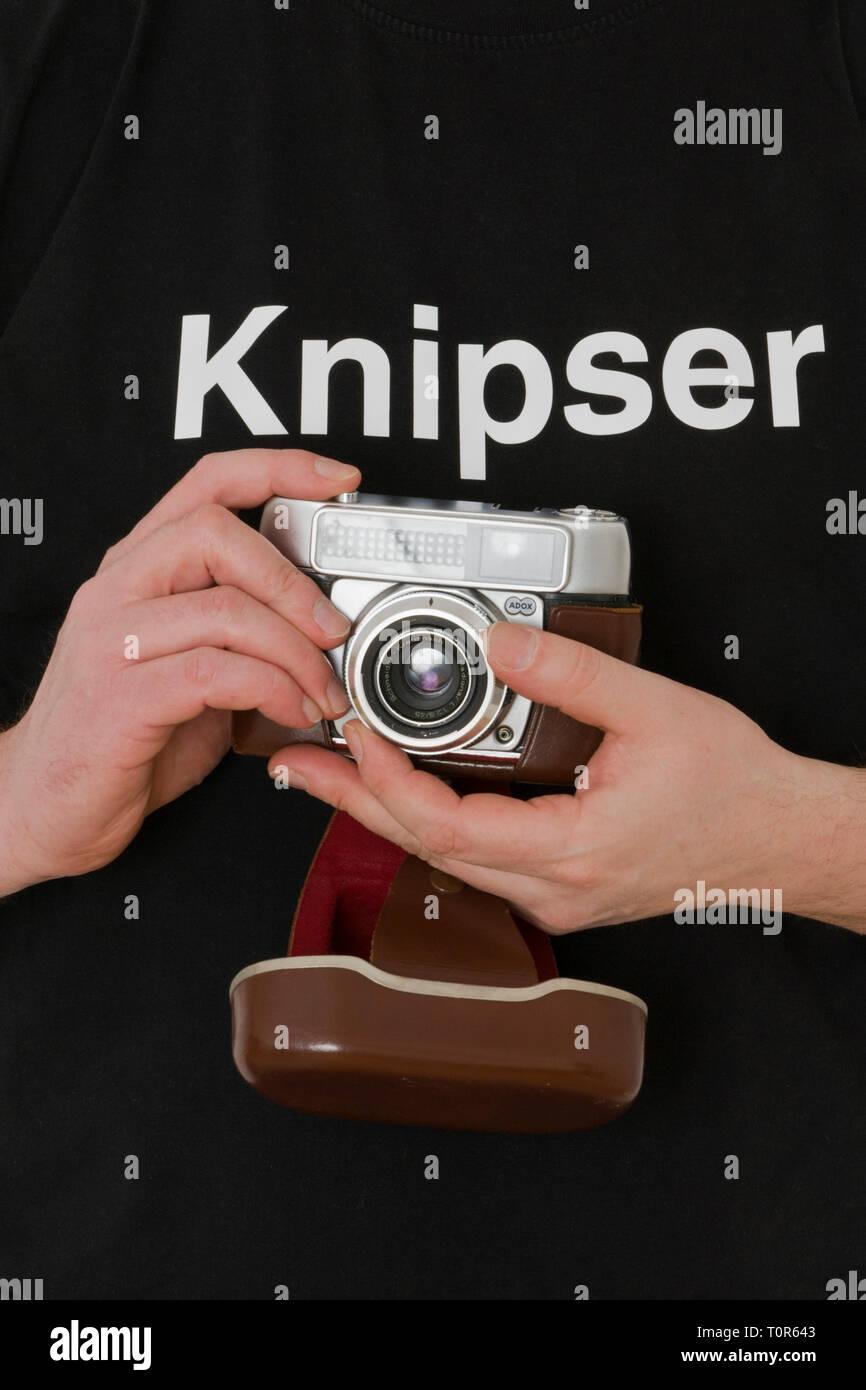 Mann mit Ändern analogueer Kamera hat ein schwarzes T-Shirt ein mit dem Knipser gedruckt ist. [(C) Dirk A. Friedrich, Sibyllastr. 20, 45136 Essen, Mobil 0 Stockbild