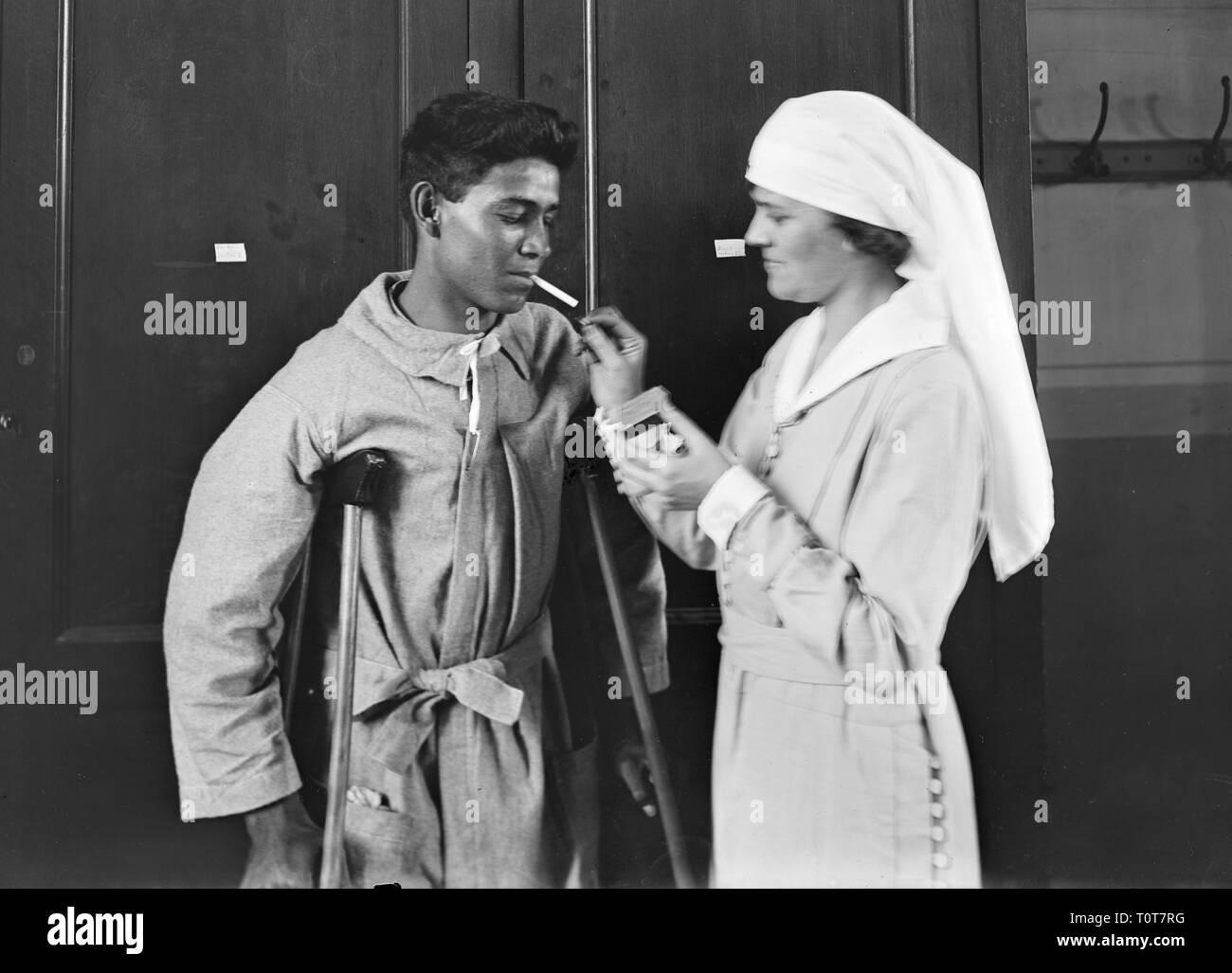 Krankenschwester leuchtet eine Zigarette für einen Patienten, Mexikanische junge bekommt einen Rauch aus dem Amerikanischen Roten Kreuz Dame 1918 Stockbild
