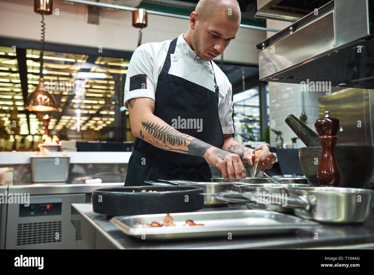 Wichtige Zutat. Junge Küchenchef brechen ein Ei für traditionelle italienische Pasta, während in einem Restaurant in der Küche stehend konzentriert. Kochen Stockfoto