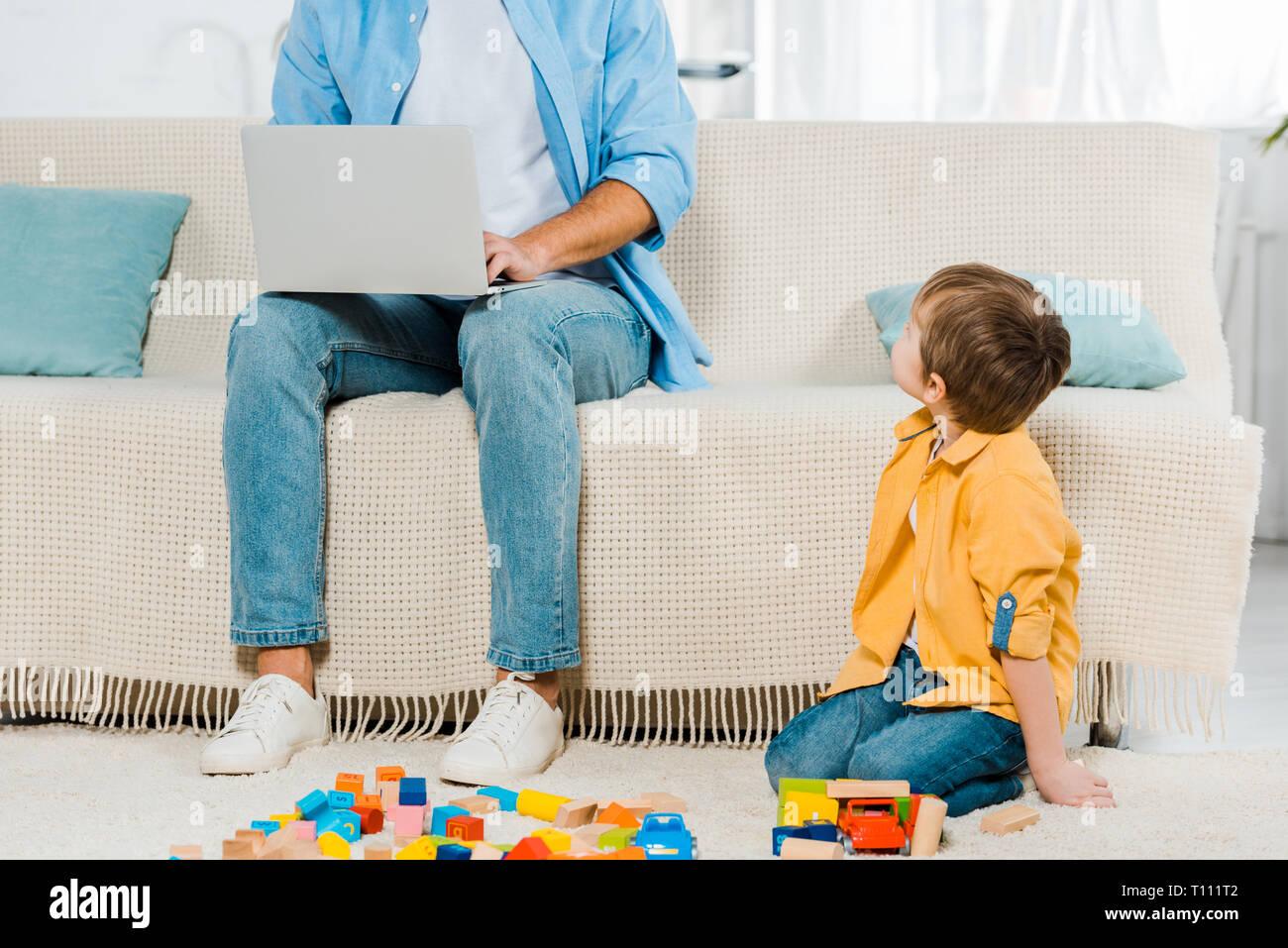 Vater saß auf der Couch und mit Laptop während Vorschüler Sohn spielen mit bunten Bausteinen zu Hause Stockfoto