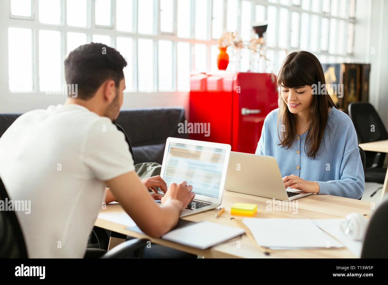 Kollegen mit Laptops am Schreibtisch im Büro Stockfoto