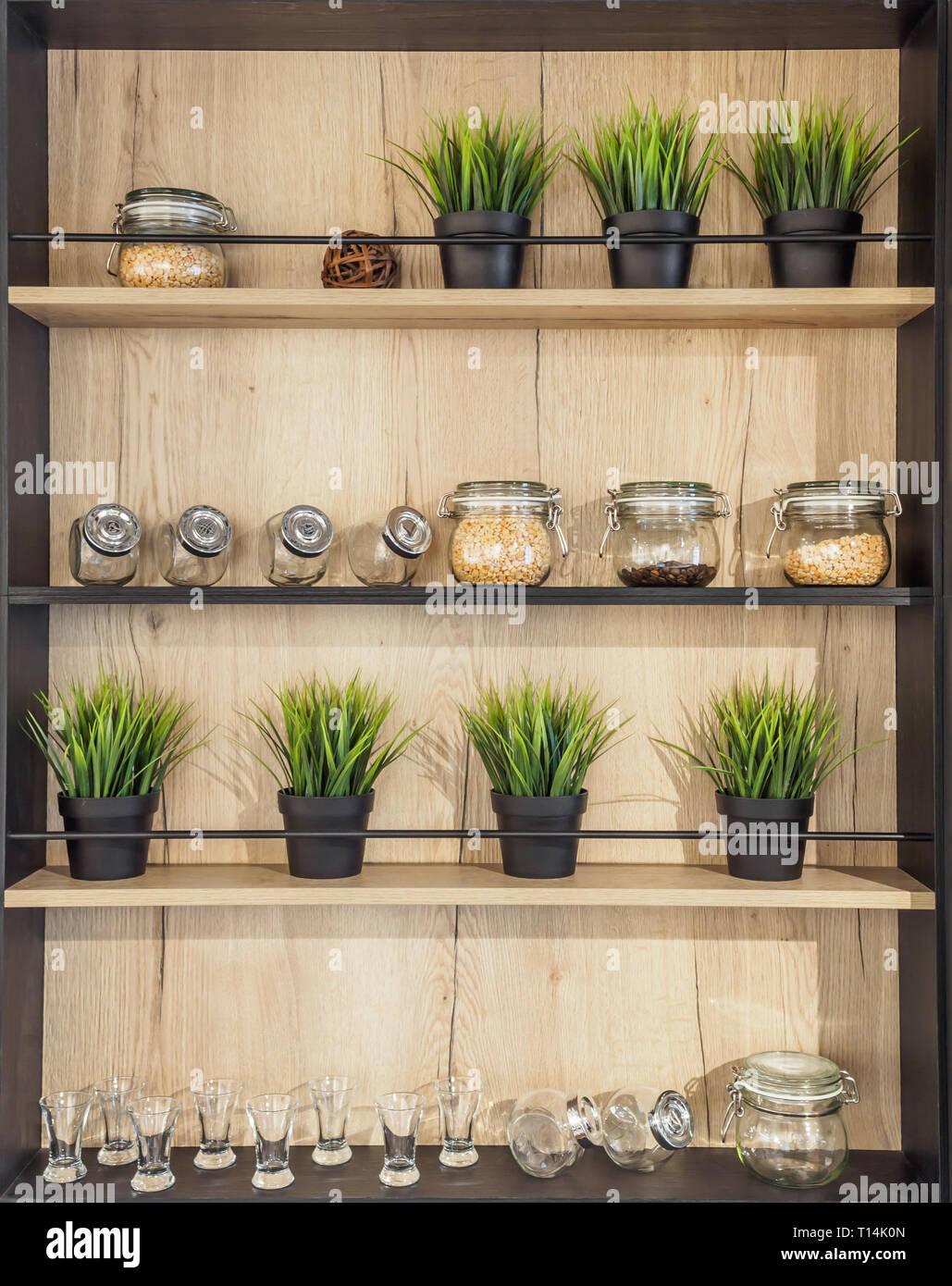 Holz- helf mit Geschirr. Gläser mit Gewürzen Topfpflanze ...