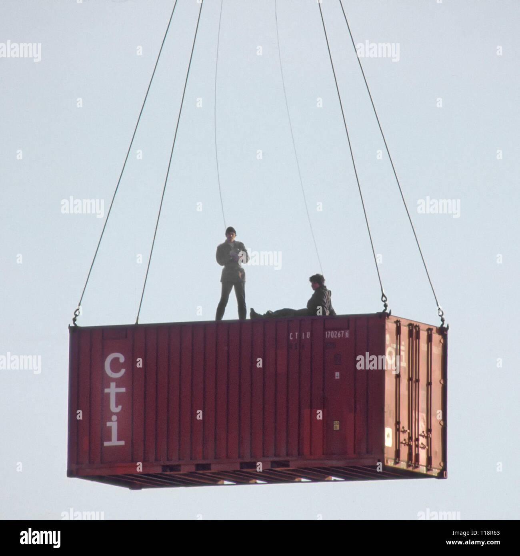 Archiv der Shipping Container Depot zeigt Kran & Kabel verschieben Container & Arbeiter an Bord anspannen Kabel ein- und ausschalten in den siebziger Jahren London England Großbritannien Stockbild
