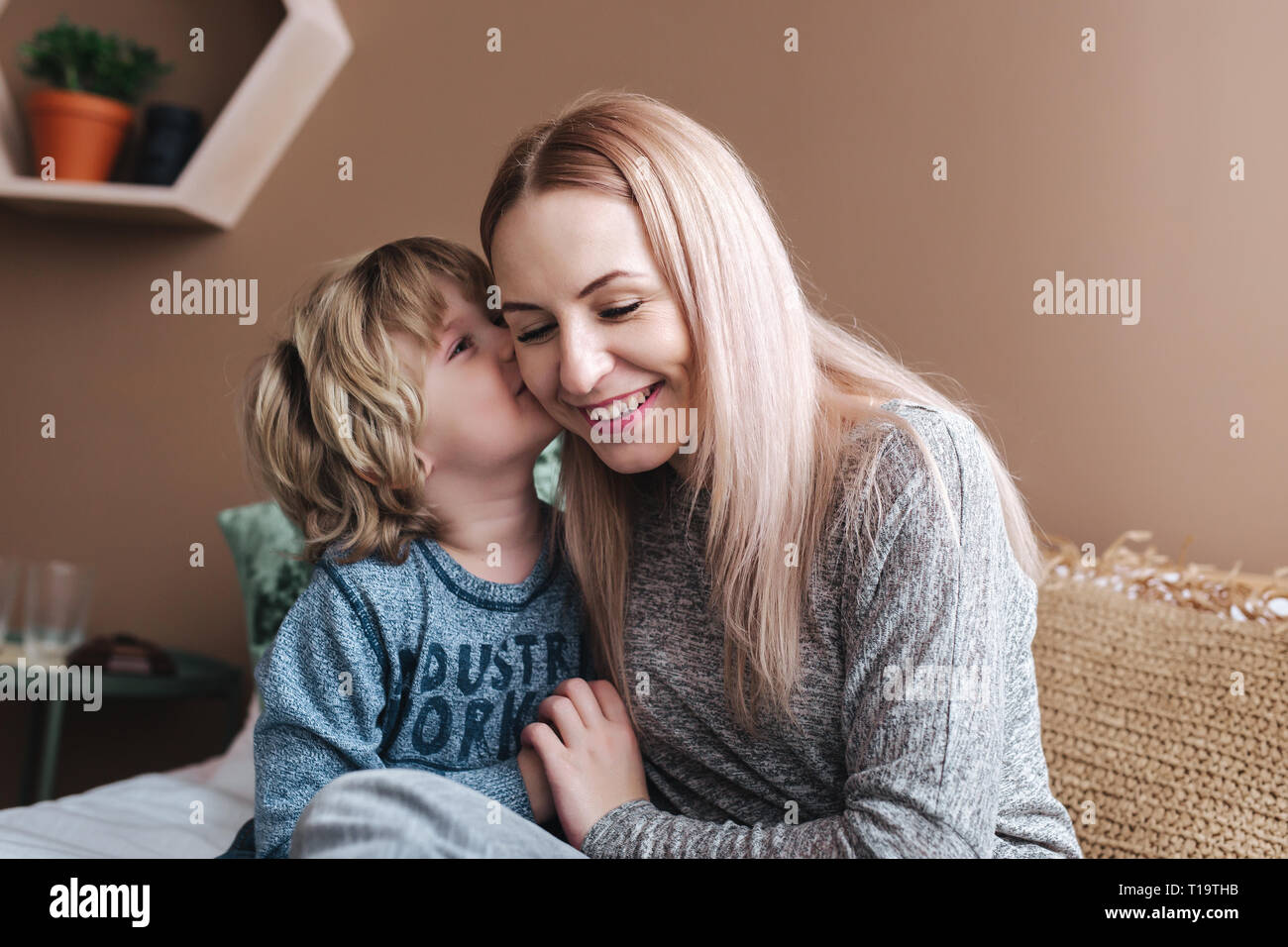 Sohn ist seiner Mutter küssen. Mutter und Sohn. Happy Mother's Day. Mutter ihr Kind zu Hause umarmen Stockfoto
