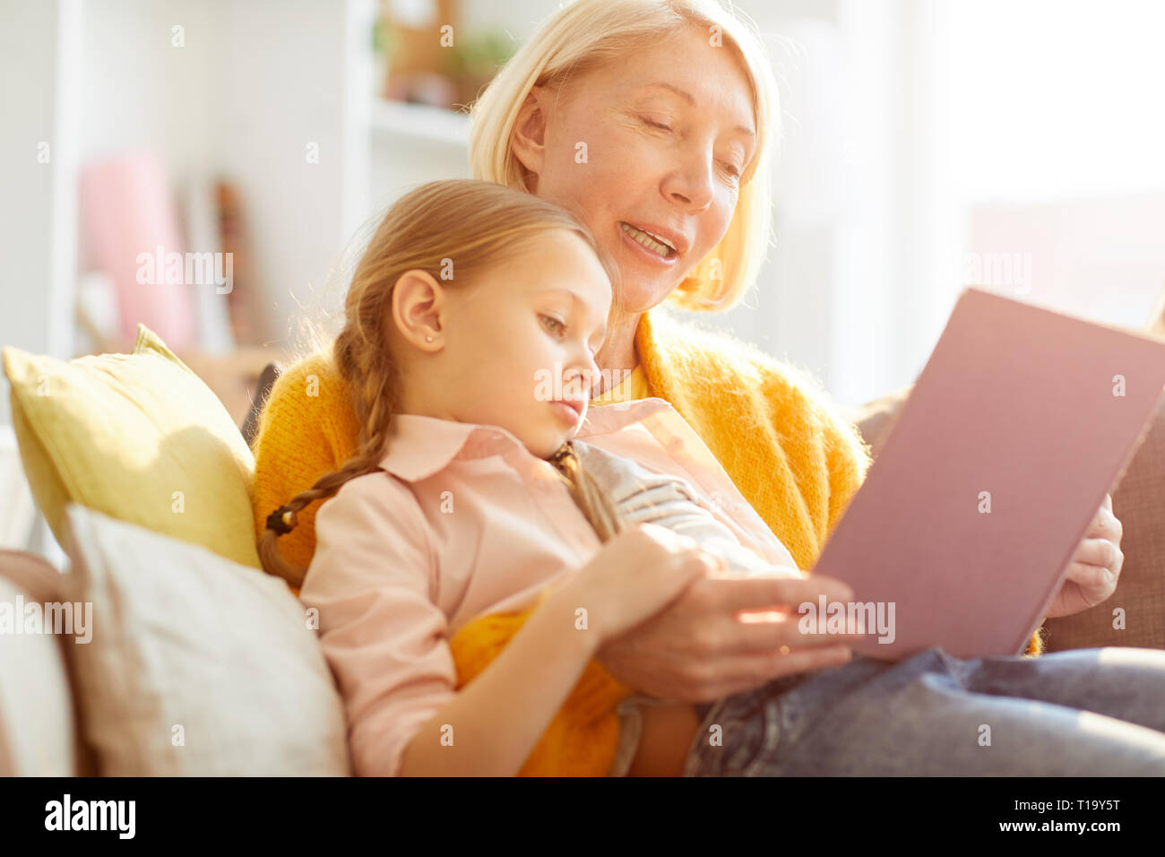 Mutter Lesung Geschichten im Sonnenlicht Stockbild