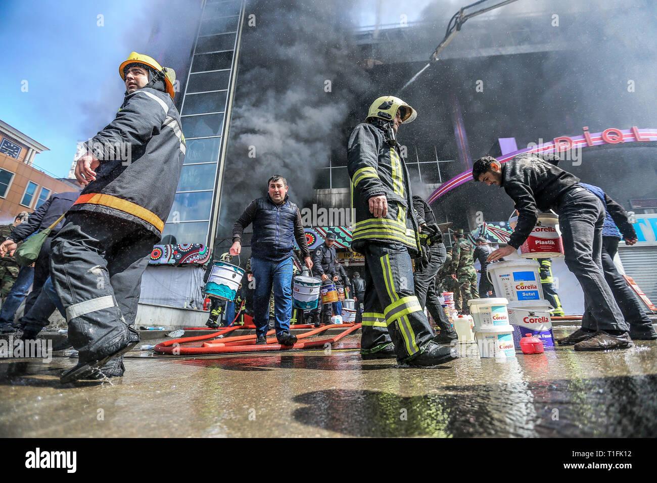 """Baku, Aserbaidschan. 26 Mär, 2019. Feuerwehrmänner Arbeiten einen Brand an Diqlas Markt in Baku, Aserbaidschan, Dienstag, 26. März 2019 zu stellen. Ein großes Feuer brach heute Morgen im Einkaufszentrum """"iglas' im Dorf 8 Kilometer in Baku. Brennen Sie die oberen Etagen des 5-stöckigen Gebäude. Credit: Aziz Karimov/Pacific Press/Alamy leben Nachrichten Stockfoto"""
