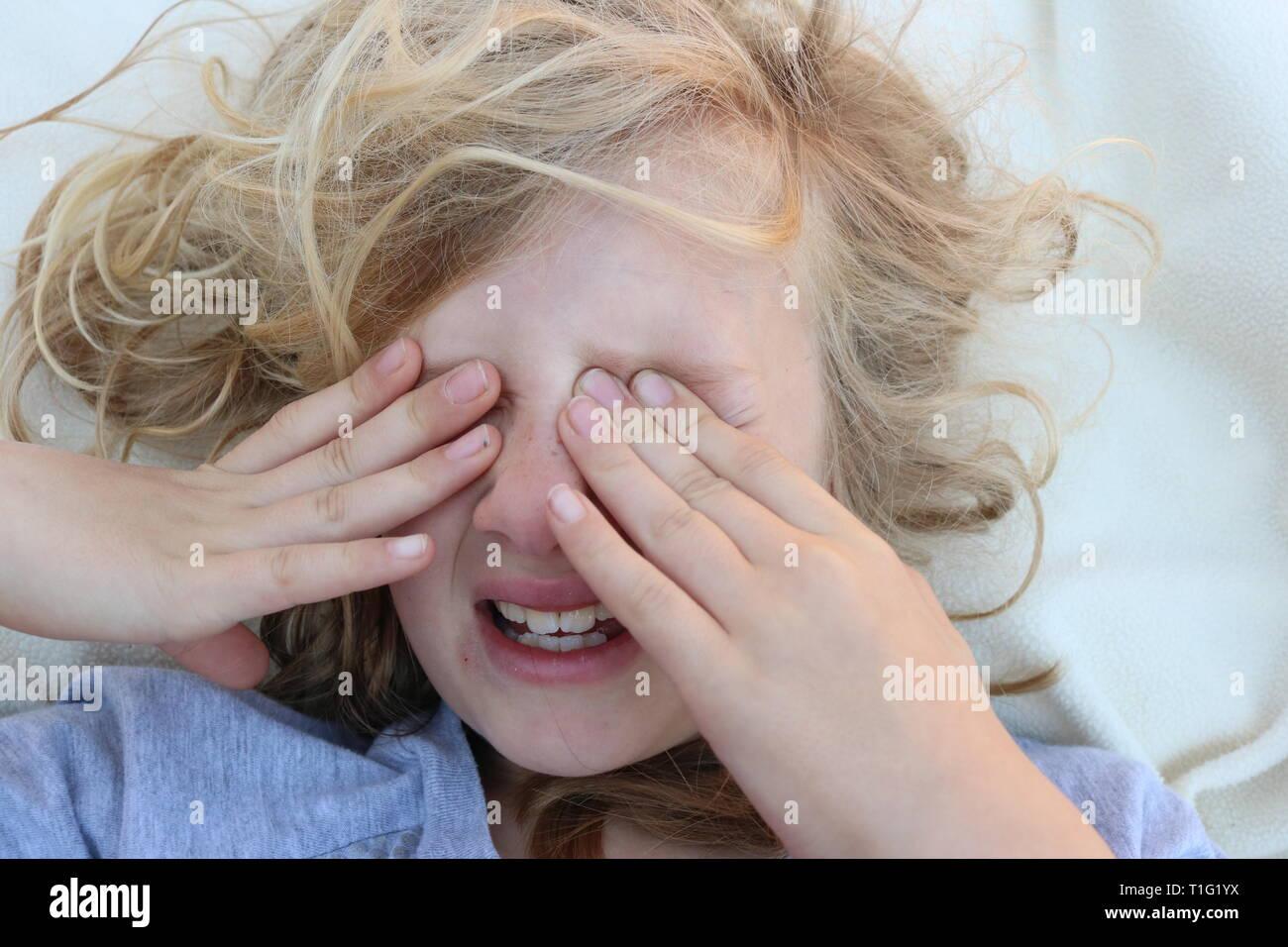 Porträt von einem müden Kind in den Schmerz mit den Händen der vor ihren Augen Stockbild